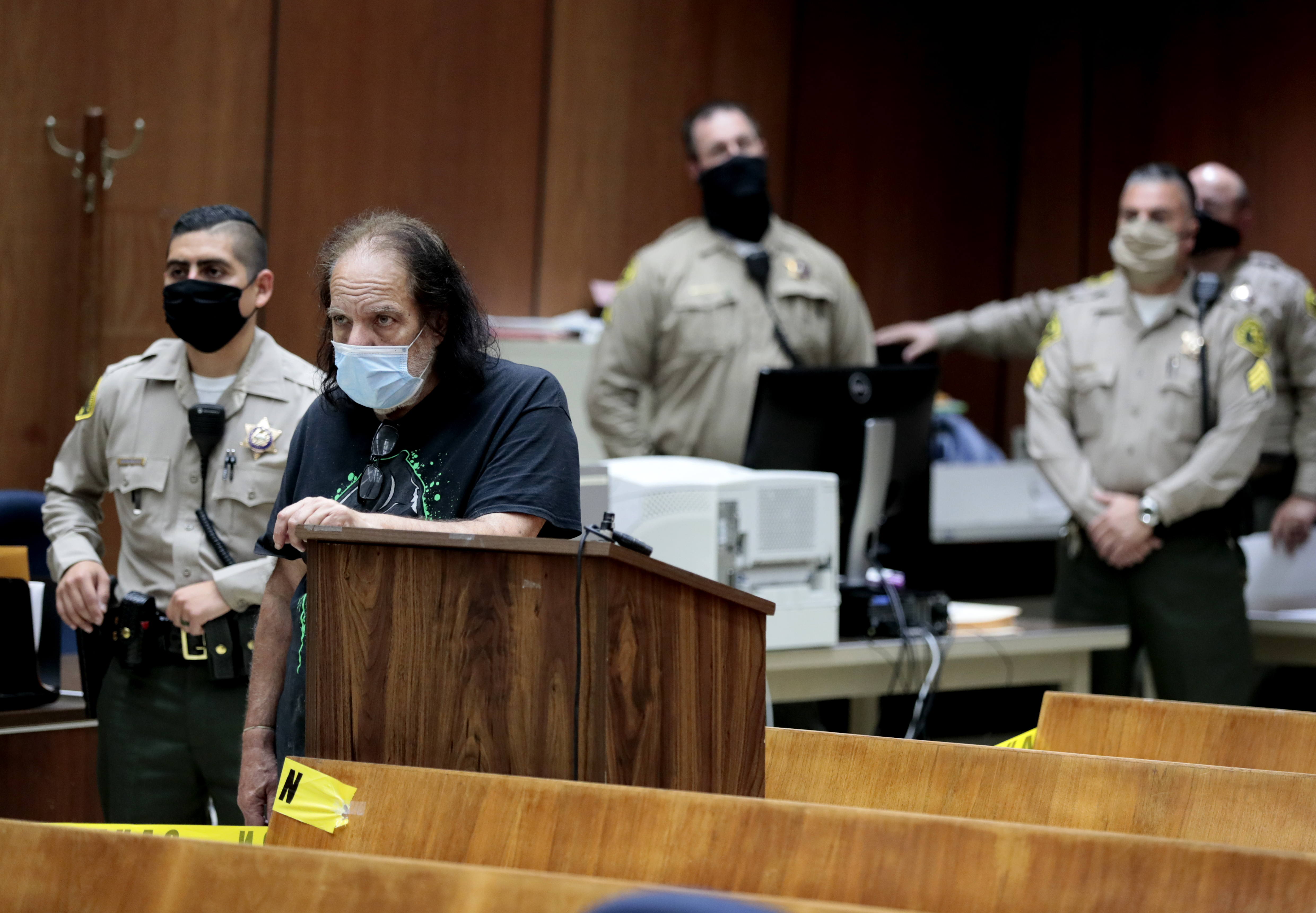 Adult film star Ron Jeremy, second from left, makes his first court appearance Tuesday, June 23, 2020, in Los Angeles. Los Angeles County prosecutors say Jeremy has been charged with raping three women and sexually assaulting a fourth. (Robert Gauthier/Los Angeles Times via AP, Pool)