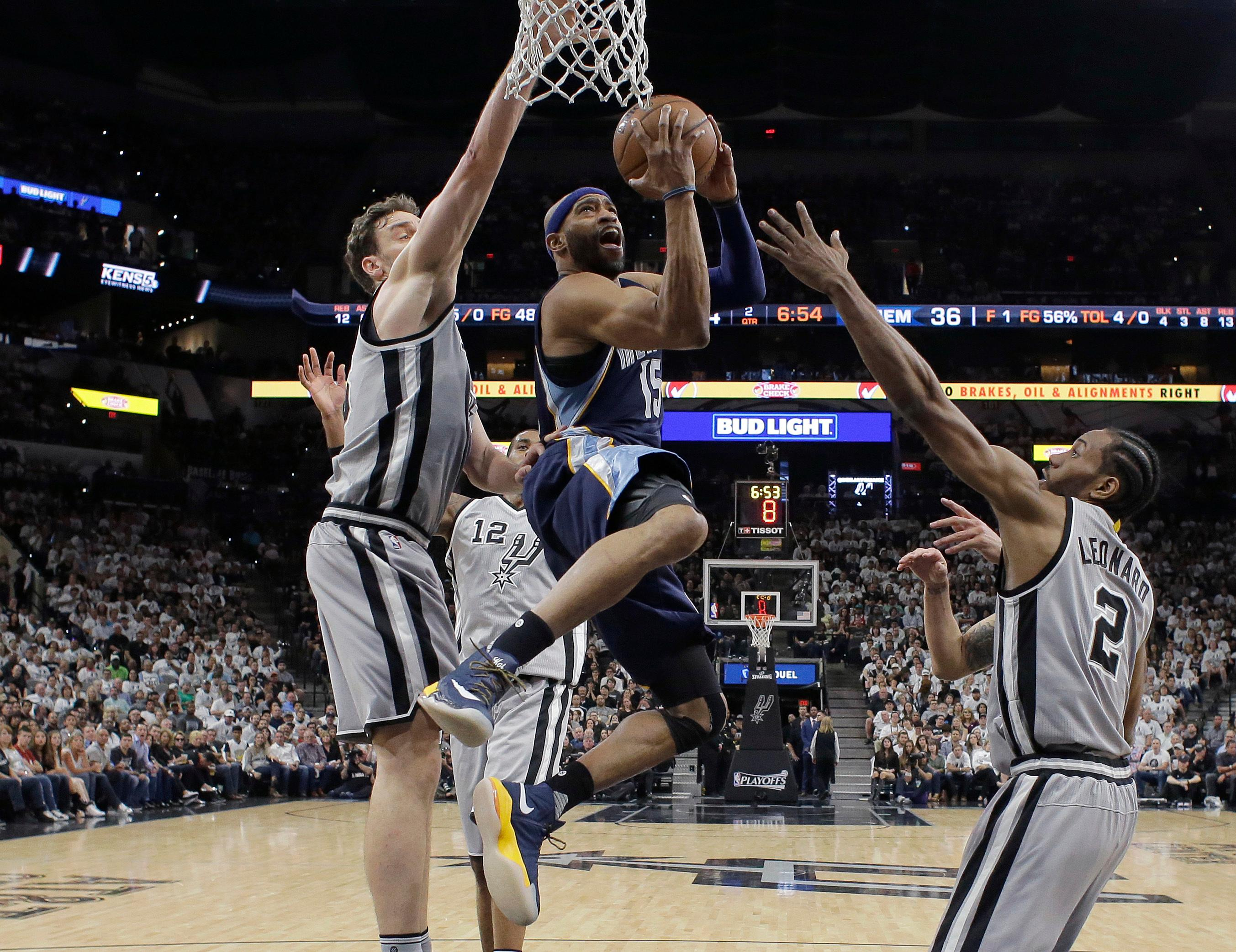 Memphis Grizzlies guard Vince Carter (15) shoots between Spurs San Antonio Spurs center Pau Gasol, left, and forward Kawhi Leonard (2) during the first half of Game 1 in a first-round NBA basketball playoff series, Saturday, April 15, 2017, in San Antonio. (AP Photo/Eric Gay)