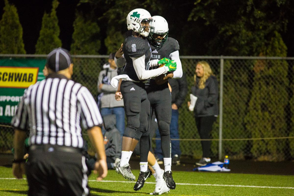 Sheldon receiver Raymond Woodie (#2) and quarterback Michael Johnson (#1) celebrate after Johnson's touchdown. On a rainy Monday evening Sheldon defeated West Salem 41-7 at home. The game had been postponed from Friday due to unhealthy levels of smoke in the atmosphere due to nearby forest fires. Photo by Dillon Vibes