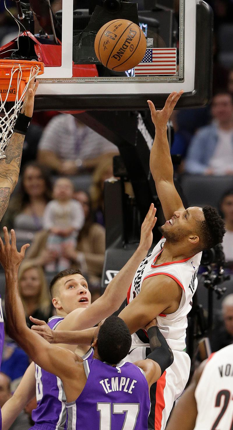 Portland Trail Blazers guard Evan Turner, right, goes to the basket over Sacramento Kings guard Bogdan Bogdanovic, left, of Serbia, and Garrett Temple, center, during the first quarter of an NBA basketball game Friday, Nov. 17, 2017, in Sacramento, Calif. (AP Photo/Rich Pedroncelli)