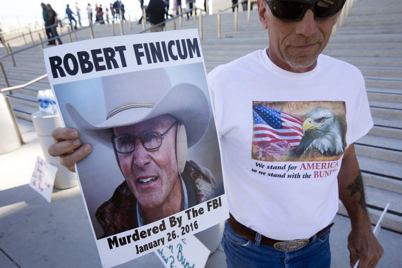 Randy Peck of Las Vegas, a supporter of Nevada rancher Cliven Bundy, holds a sign featuring Arizona rancher LaVoy Finicum in front of the U.S. Courthouse in downtown Las Vegas Thursday, March 10, 2016. Bundy is facing charges that he led an armed standoff against federal agents two years ago. (Steve Marcus/Las Vegas Sun via AP) LAS VEGAS REVIEW-JOURNAL OUT; MANDATORY CREDIT
