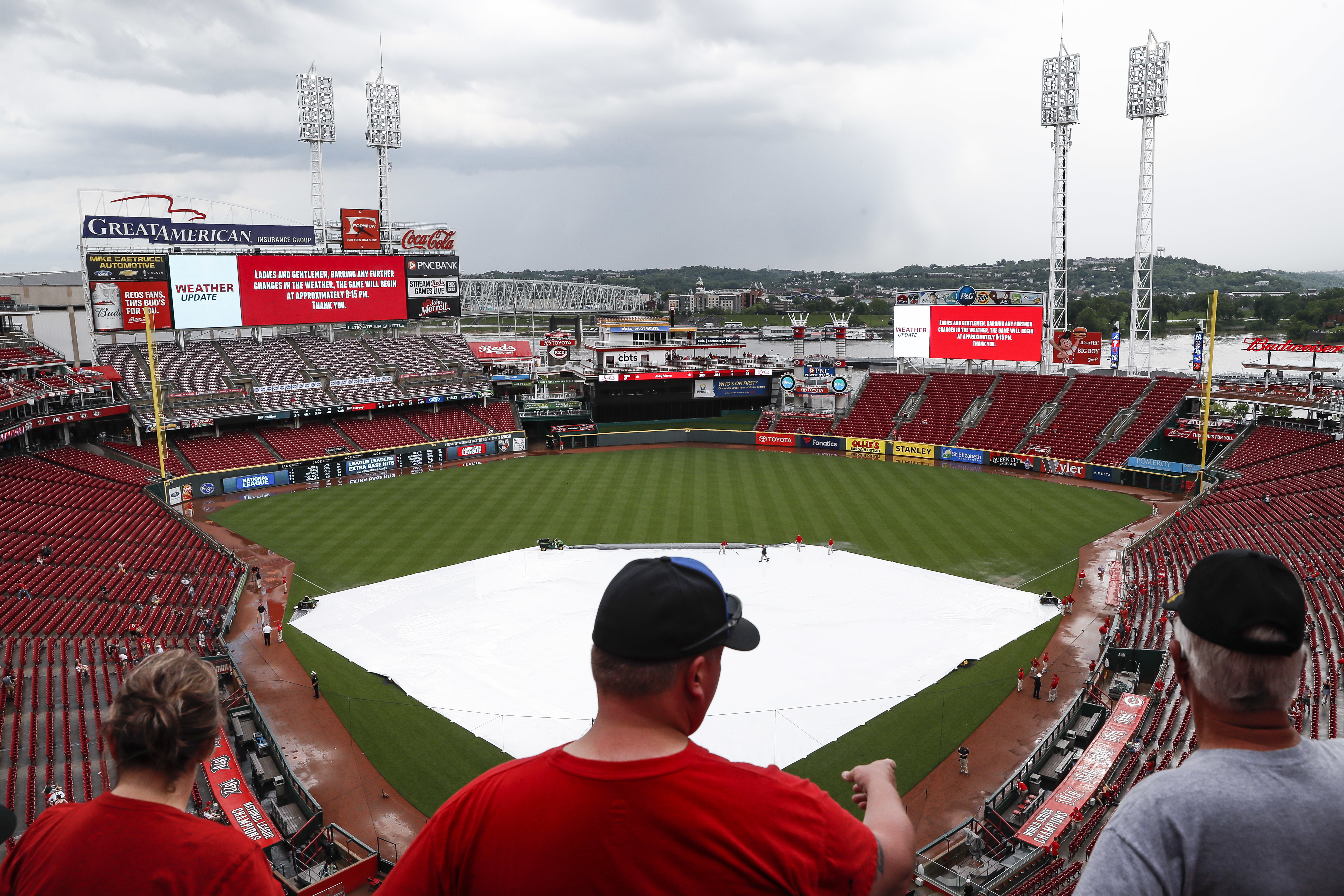 Fans wait in the stands during a rain delay before a baseball game between the Cincinnati Reds and the Pittsburgh Pirates, Tuesday, May 22, 2018, in Cincinnati. (AP Photo/John Minchillo)