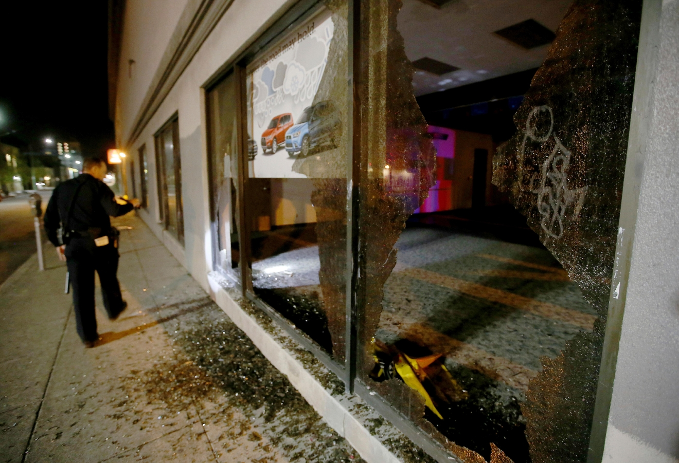 An Oakland police officer checks out damage after a window was broken by protesters at a car dealership in downtown Oakland, Calif., on Wednesday, Nov. 9, 2016. President-elect Donald Trump's victory set off multiple protests. (Jane Tyska/Bay Area News Group via AP)