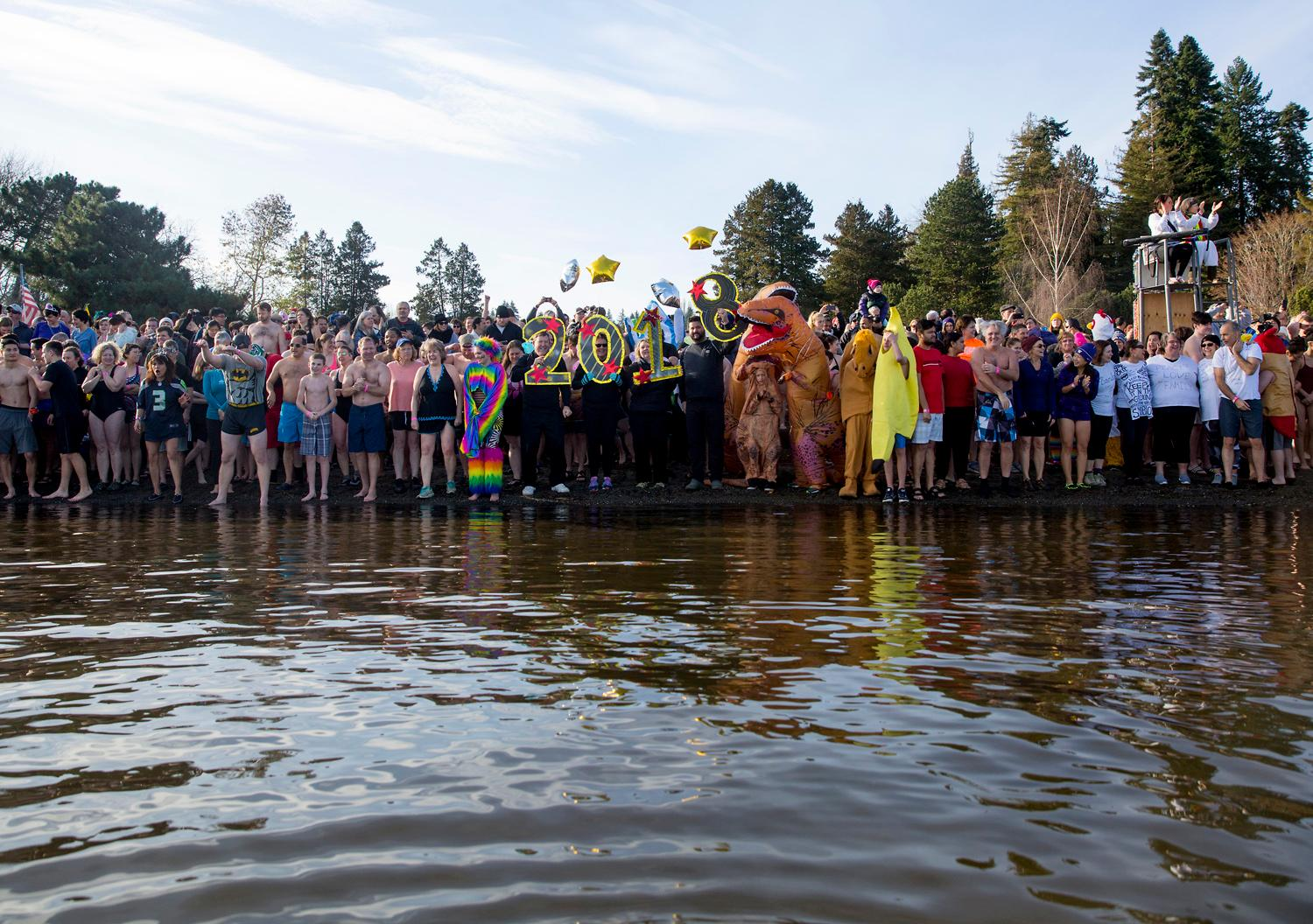 Happy New Year! How are you spending the first day of 2018? Thousands of people spent it in the freezing cold waters of Lake Washington at high noon exactly, as part of the annual Polar Bear Plunge. Costumes were encouraged as participants gathered at Matthews Beach beforehand, and had warm resfreshments waiting for them afterwards! Limited Badges of Courage were awarded to those who darned to fully submerge…..HAPPY 2018! January 1, 2018. (Image: Sy Bean / Seattle Refined)