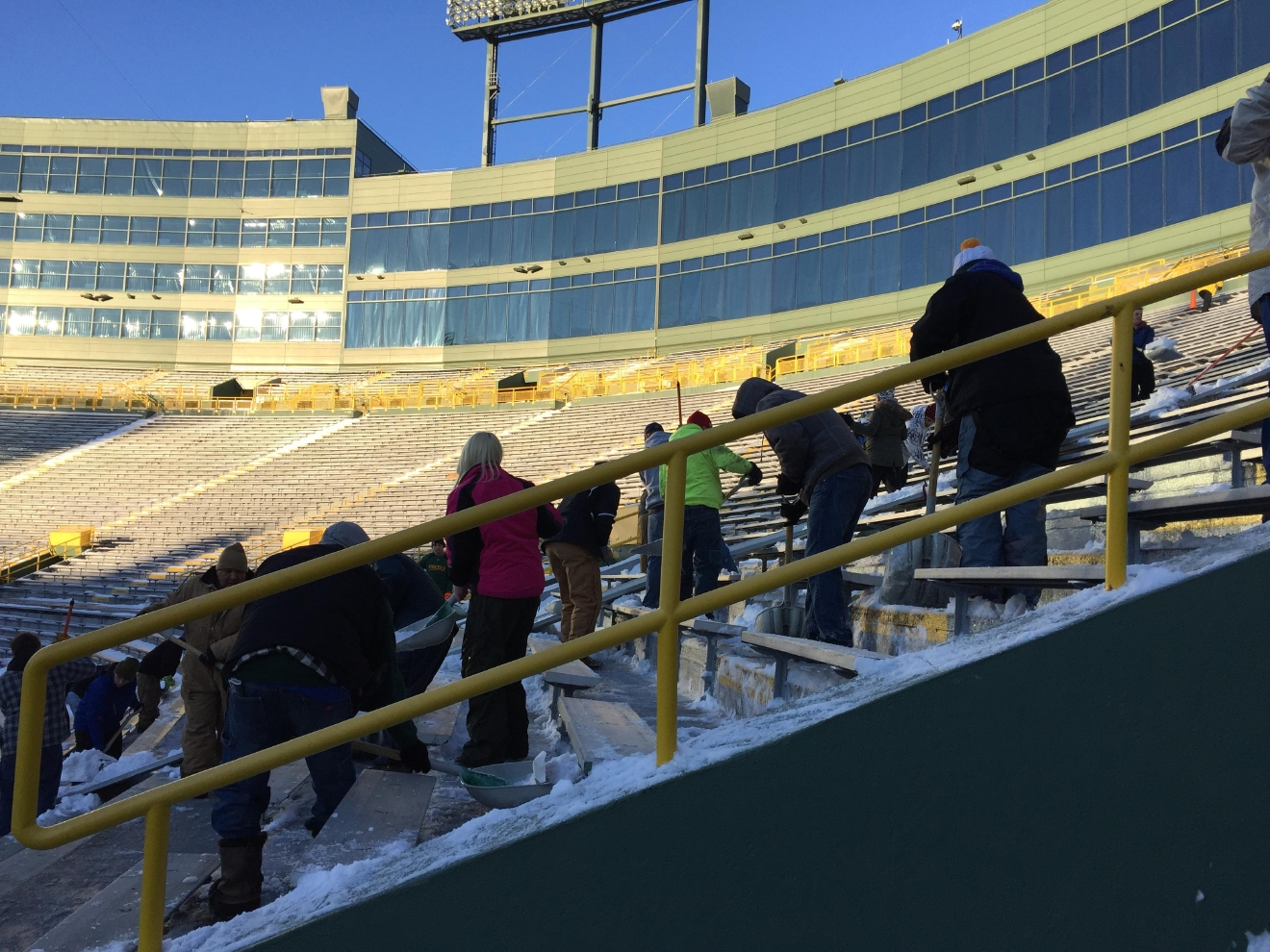 Green Bay Packers fans shovel out bleachers in Lambeau Field's north end zone, Dec. 22, 2016. (WLUK/Andrew LaCombe)
