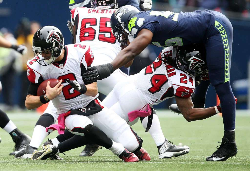 Seahawks defensive lineman Cliff Avril, left, reaches out to sack Falcons quarterback Matt Ryan (2) in the second quarter of Seattle's game against Atlanta, Sunday Oct. 16, 2016, at CenturyLink Field. (Photo: Genna Martin, seattlepi.com)