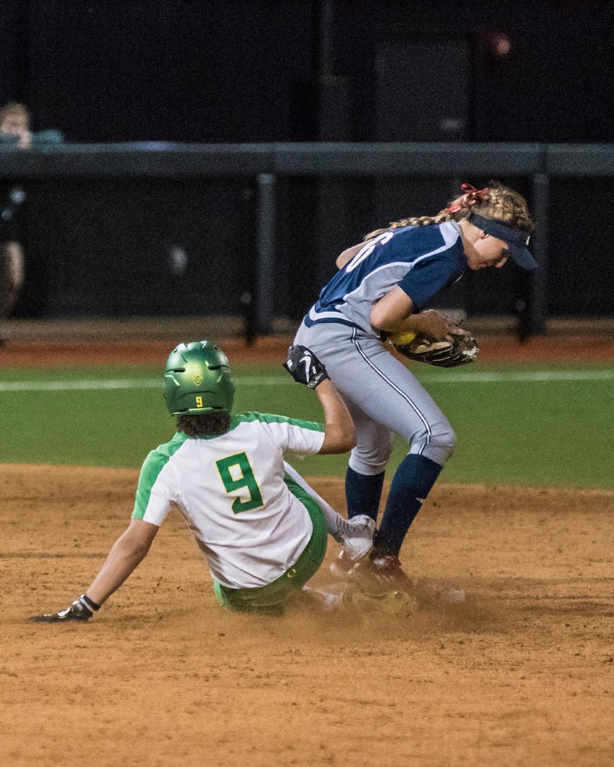 Oregon Ducks Shannon Rhodes (#9) slides into second as second base player Kayla Wedl (#6) attempts to get the out.The No. 3 Oregon Ducks defeated the University of Illinois Chicago Flames 13-0 with the run-rule on Saturday night at Jane Sanders Stadium. The Ducks scored in every inning and then scored nine runs at the bottom of the fourth. The Oregon Ducks are now 22-0 in NCAA regional games. The Oregon Ducks play Wisconsin next on Saturday, May 20 at 2pm at Jane Sanders Stadium. Photo by Cheyenne Thorpe, Oregon News Lab