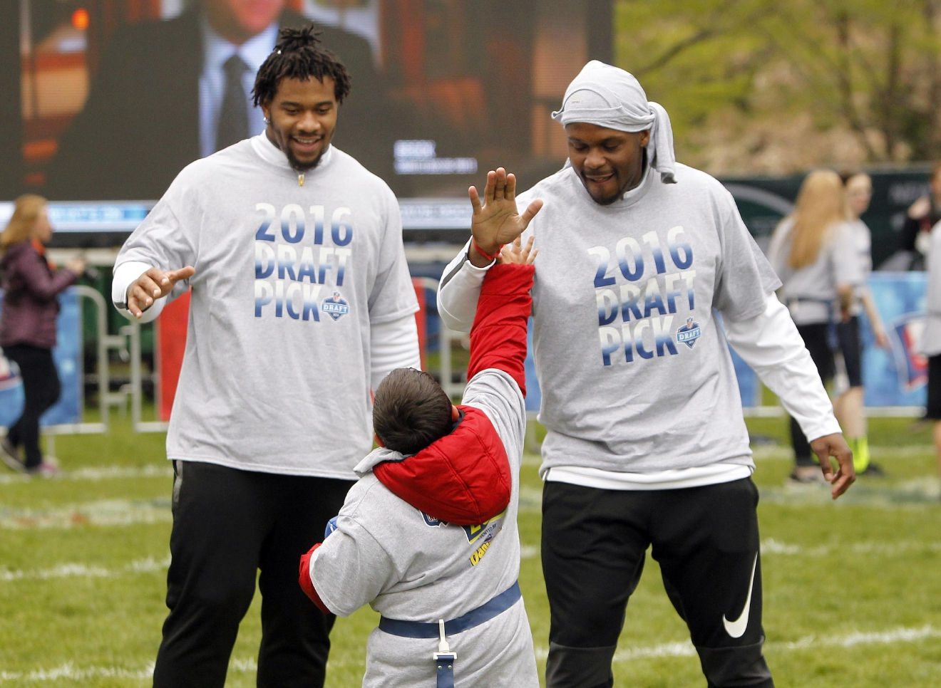 Mississippi's Robert Nkemdiche, left, and Alabama's Reggie Ragland gives high fives during an NFL Play 60 event at Grant Park, Wednesday, April 27, 2016, in Chicago before Thursday's first round of the NFL football draft. (AP Photo/Kiichiro Sato)