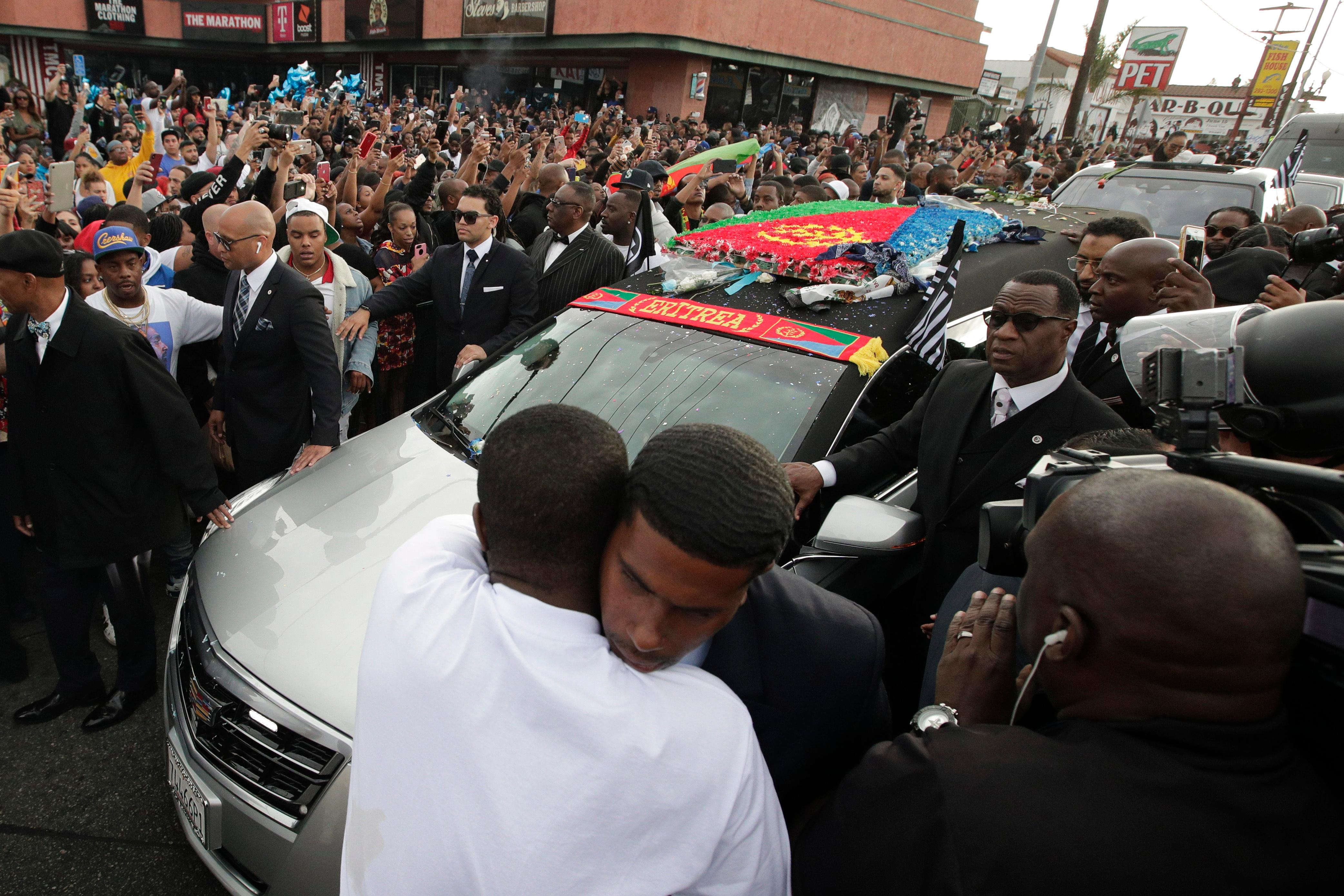 Two men hug as a hearse carrying the casket of slain rapper Nipsey Hussle passes through the crowd Thursday, April 11, 2019, in Los Angeles. (AP Photo/Jae C. Hong)