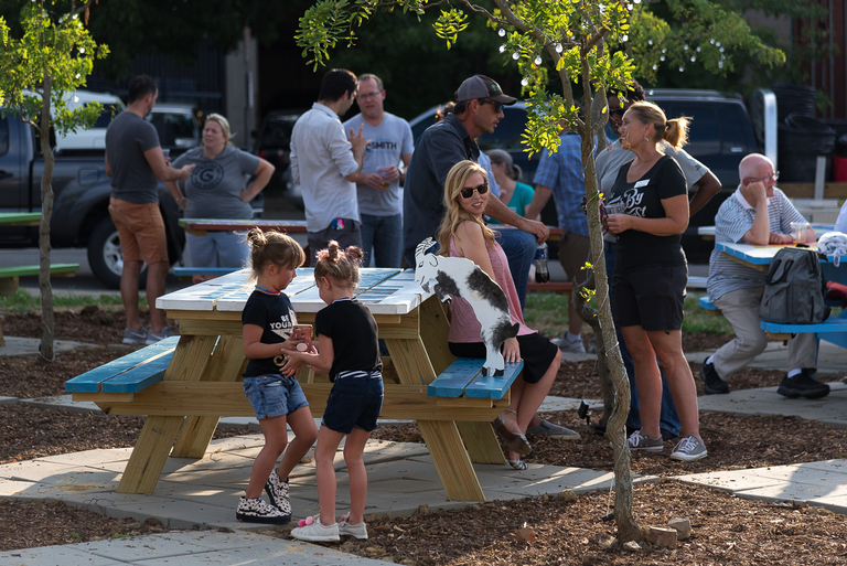 The green space at 620 Scott Street in Covington was recently transformed into a temporary park themed around Alice in Wonderland. Dubbed Madhatter Park, its transformation was fueled entirely by volunteers in the community. The park now features decorated picnic tables, solar-powered string lights hanging on nearby trees, a freshly painted sunflower mural, colorful two-person chairs made from reclaimed materials, a sunflower wall, several community garden beds, and ample space to play ball. On Thursday, August 2, Renaissance Covington and other local organizations who helped build the park celebrated a ribbon-cutting with live music, beer, and a food truck. The park will be maintained through fall 2018. / Image: Phil Armstrong, Cincinnati Refined // Published: 8.7.18