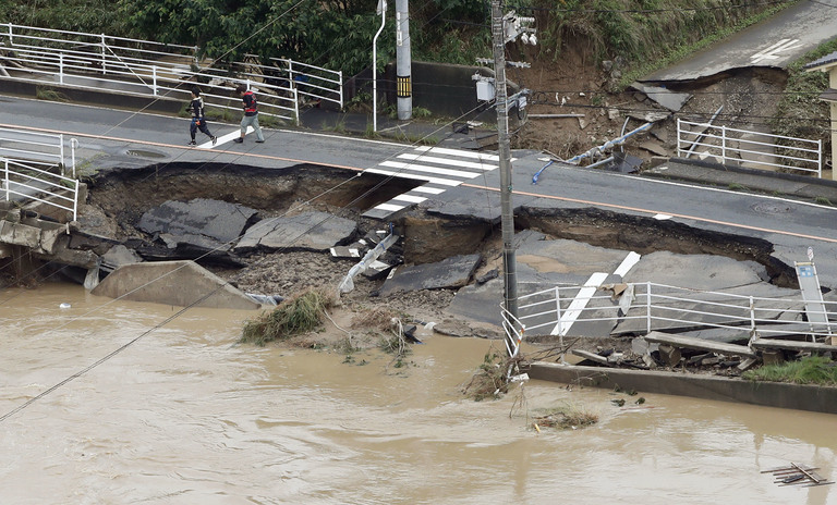 A road is damaged by flood water following heavy rain in Kurashiki city, Okayama prefecture, southwestern Japan, Sunday, July 8, 2018. Heavy rainfall hammered southern Japan for the third day, prompting new disaster warnings on Kyushu and Shikoku islands on Sunday. (Shohei Miyano/Kyodo News via AP)