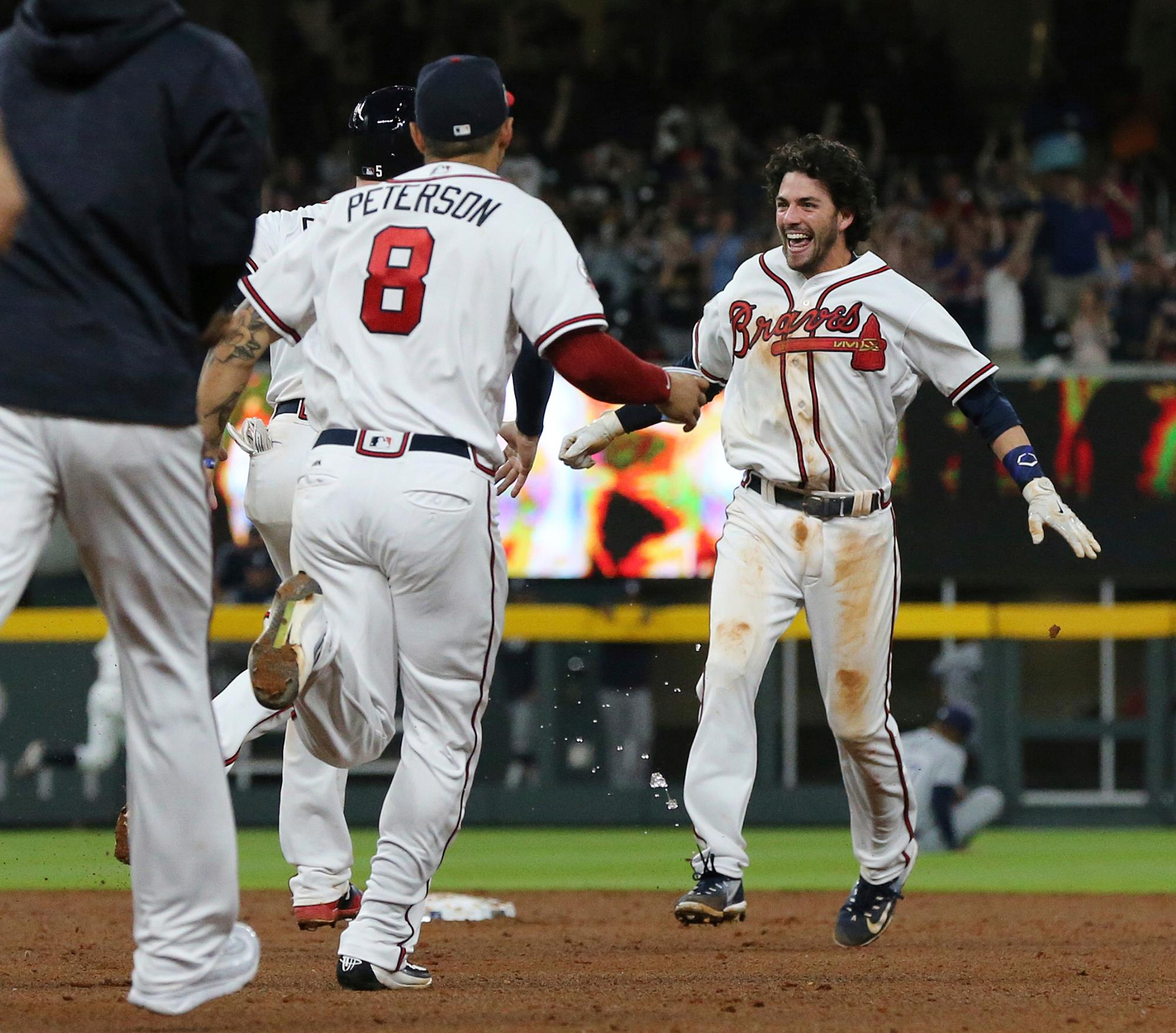 The Atlanta Braves rush the field to celebrate Dansby Swanson as he hits a walk-off single to beat the San Diego Padres, 5-4, in the ninth inning of a baseball game in Atlanta on Monday, April 17, 2017. (Curtis Compton/Atlanta Journal-Constitution via AP)