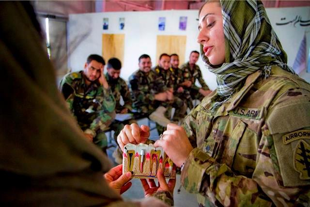 U.S. Army Spc. Kassandra Torres, right, shows Afghan commando medics the proper way to floss during a basic dental class on Forward Operating Base Thunder in Paktya province, Afghanistan, July 21, 2013.