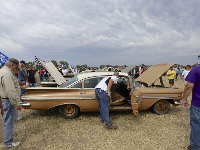 Car buffs survey a 1959 Chevrolet Impala, foreground, and other Chevrolet vehicles for sale in the auction of vintage cars and trucks from the former Lambrecht Chevrolet dealership in Pierce, Neb.