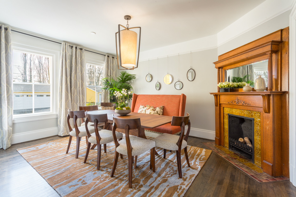 The spacious dining room features the original fireplace, and carefully renovated original windows.