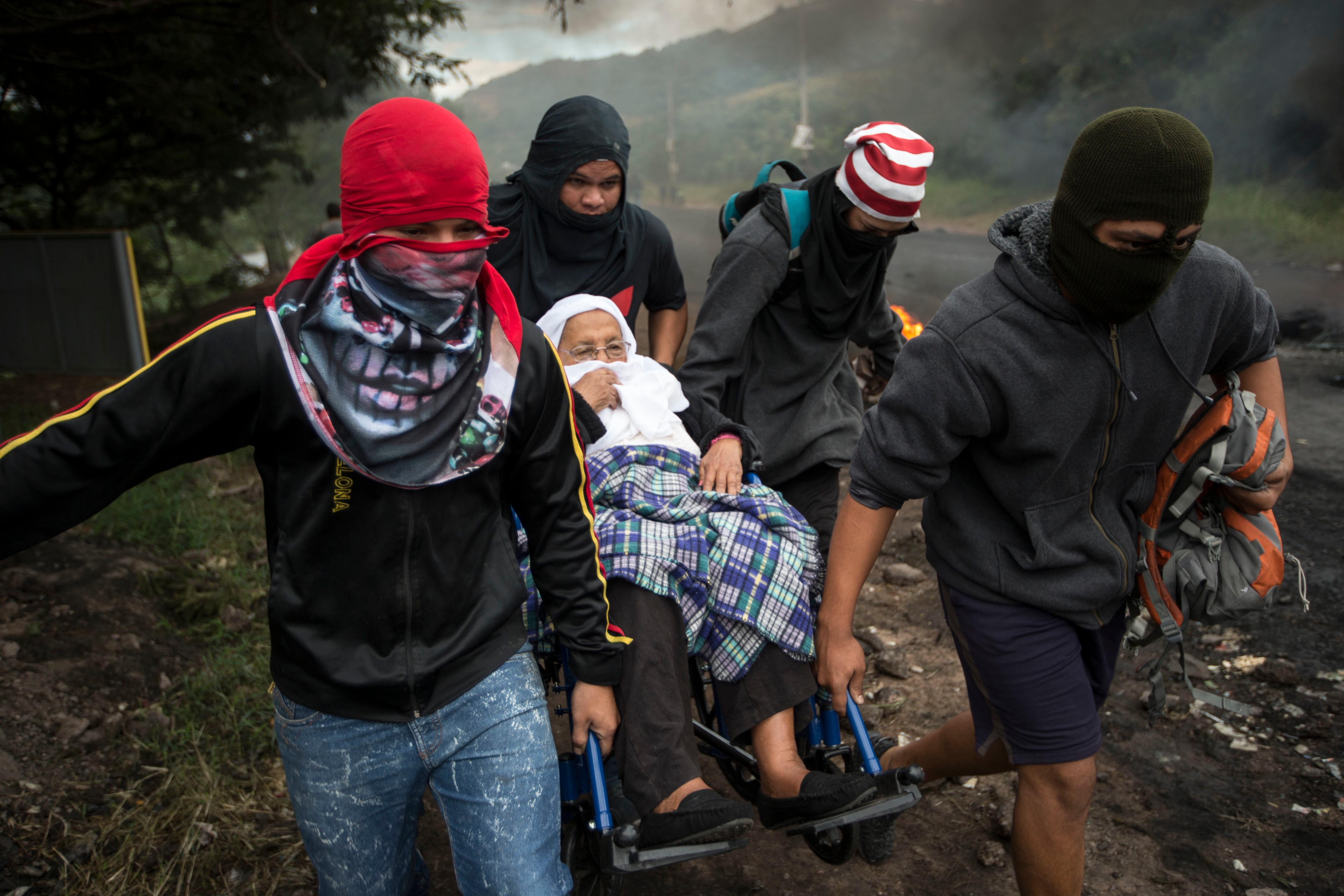 Anti-government demonstrators help a woman in a wheelchair get past a burning barricade they erected to block the road to Valle de los Angeles, on the outskirts of Tegucigalpa, Honduras, Thursday, Dec. 7, 2017. Eight Latin American governments on Wednesday applauded Honduras' willingness to recount disputed votes in the presidential elections, but questions remain about how thorough that recount will be. (AP Photo/Moises Castillo)