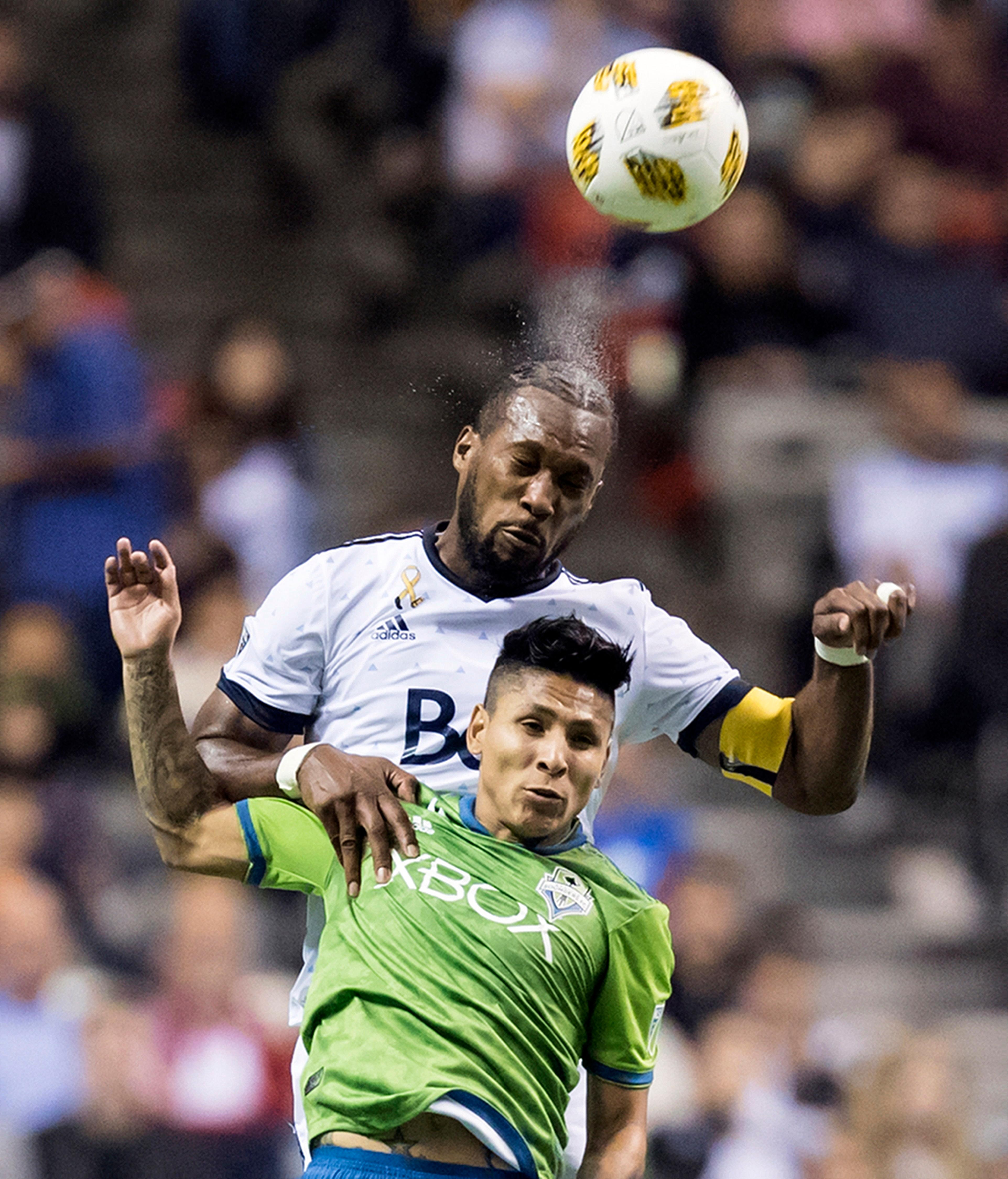 Vancouver Whitecaps' Kendall Waston, back, heads the ball behind Seattle Sounders' Raul Ruidiaz during the first half of an MLS soccer match, Saturday, Sept. 15, 2018, in Vancouver, British Columbia. (Darryl Dyck/The Canadian Press via AP)