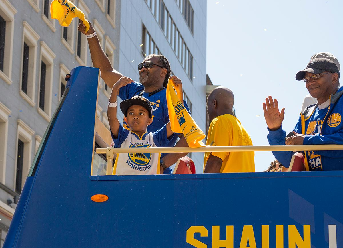 Faithful supporters atop Golden State Warriors player Shaun Livingston's double decker bus wave to the crowd. Photo by Emily Gonzalez, Oregon News Lab.