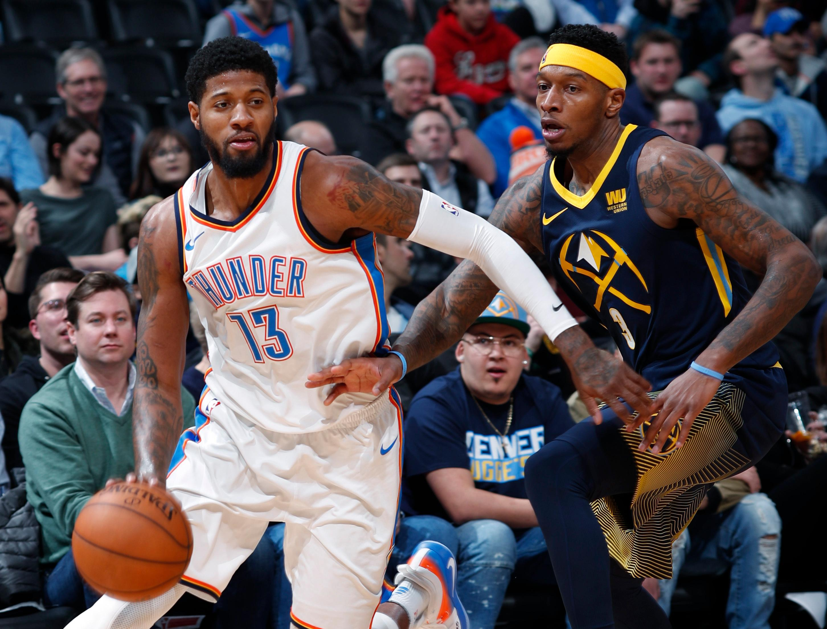 Oklahoma City Thunder forward Paul George, left, works against Denver Nuggets guard Torrey Craig during the first half of an NBA basketball game Thursday, Feb. 1, 2018, in Denver. (AP Photo/David Zalubowski)