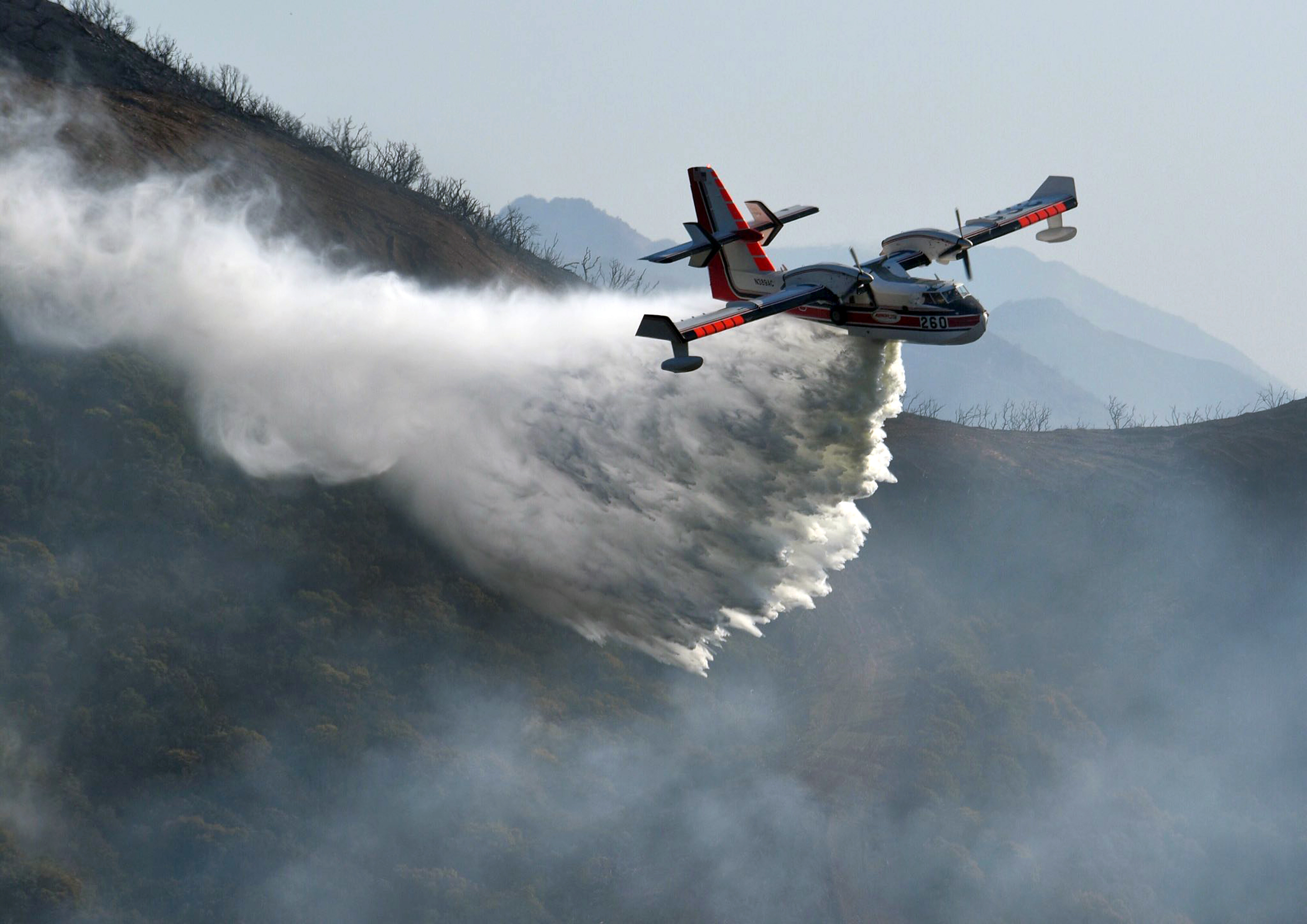 In this photo provided by the Santa Barbara County Fire Department, a Bombardier 415 Super Scooper makes a water drop on hot spots along the hillside east of Gibraltar Road in Santa Barbara, Calif., Sunday morning, Dec. 17, 2017. One of the largest wildfires in California history is now 40 percent contained but flames still threaten coastal communities as dry, gusty winds are predicted to continue. (Mike Eliason/Santa Barbara County Fire Department via AP)