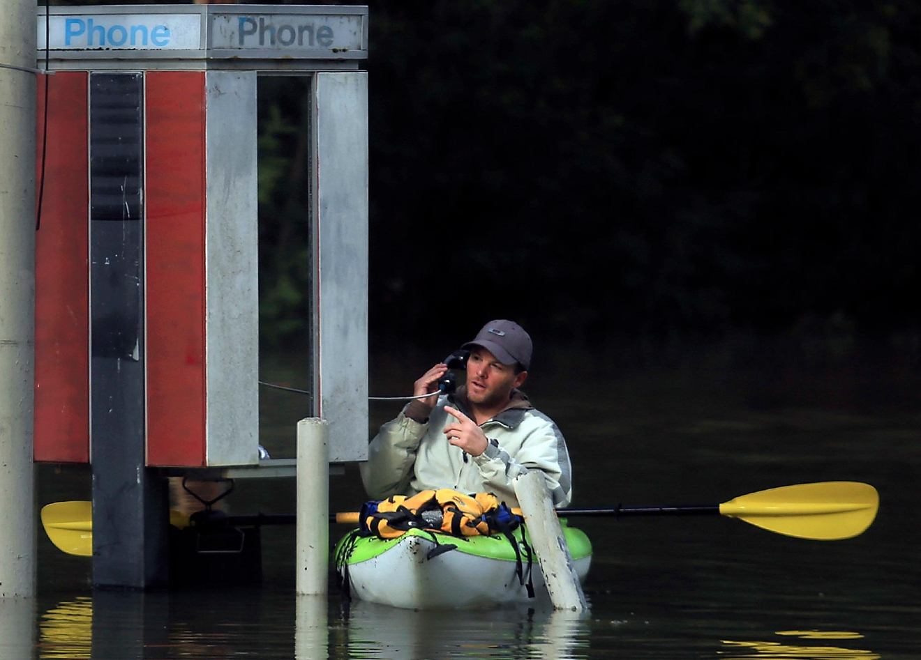 With Russian River waters rising, Dustin Coupe of Guerneville talks with an operator via phone booth on River Road in Guerneville, Calif., Wednesday. Jan. 11, 2017. Dozens of Northern California residents have been rescued by boats and firetrucks from flooded homes near Hollister, California as a drought-busting series of storms moved out of the region. Days of rain and snow have toppled trees and forced people out of water-logged homes.  (Kent Porter/The Press Democrat via AP)