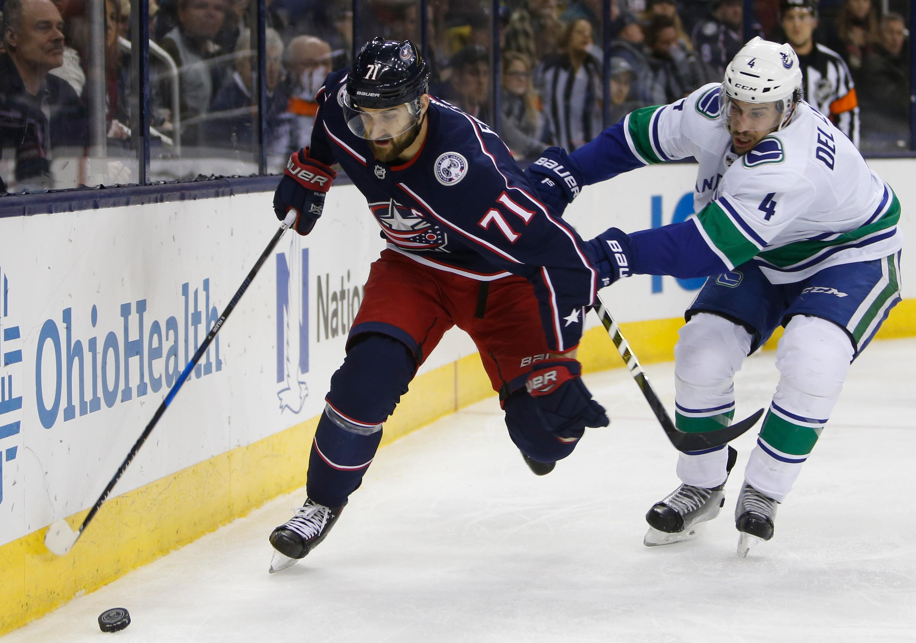 Columbus Blue Jackets' Nick Foligno, left, controls the puck as Vancouver Canucks' Michael Del Zotto defends during the second period of an NHL hockey game Friday, Jan. 12, 2018, in Columbus, Ohio. (AP Photo/Jay LaPrete)
