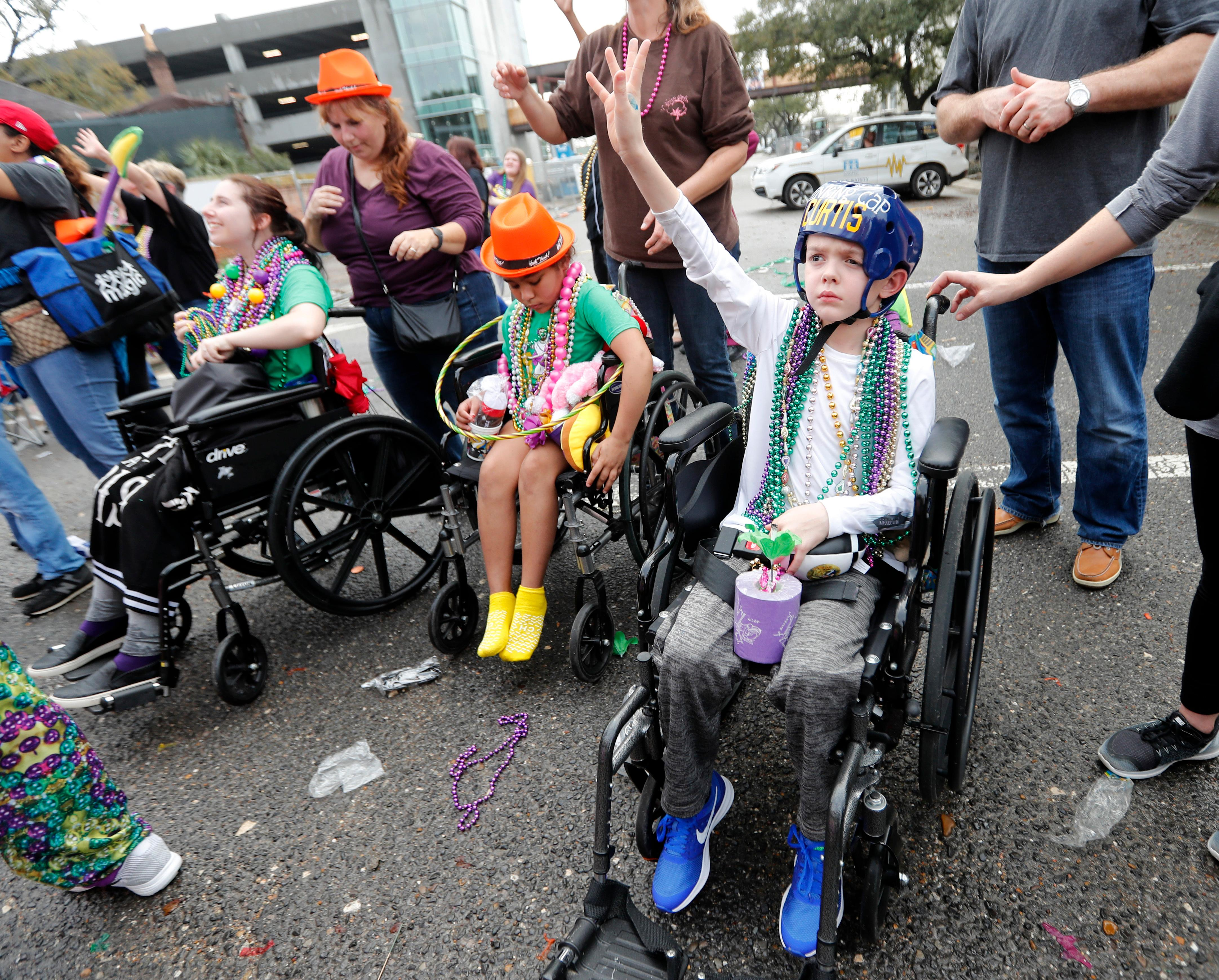 Patients from Children's Hospital of New Orleans wave for beads and trinkets outside the facility during the Krewe of Thoth Mardi Gras parade in New Orleans, Sunday, Feb. 11, 2018. The krewe's original parade route was designed specifically to serve people who were unable to attend other parades in the city. The route passes in front of several extended healthcare facilities. Carnival season will culminate on Mardi Gras day this Tuesday, Feb. 13. (AP Photo/Gerald Herbert)