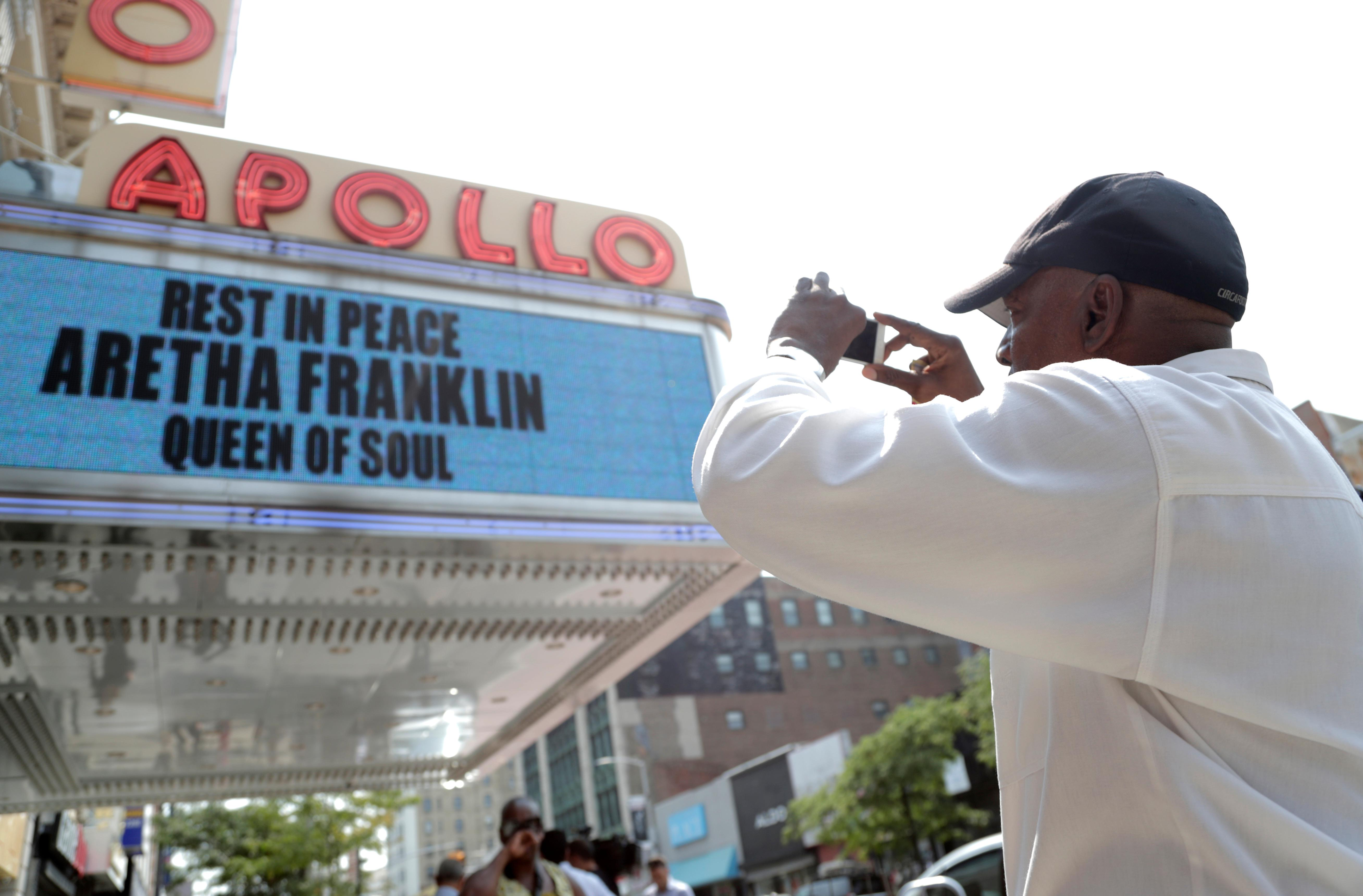 Ernie Spencer, of Westchester, N.Y., takes a photo of the marquee at the Apollo Theater, which displays a message honoring singer Aretha Franklin, Thursday, Aug. 16, 2018, in the Harlem section of New York. Franklin died in her home in Detroit at age 76 from pancreatic cancer. (AP Photo/Julio Cortez)