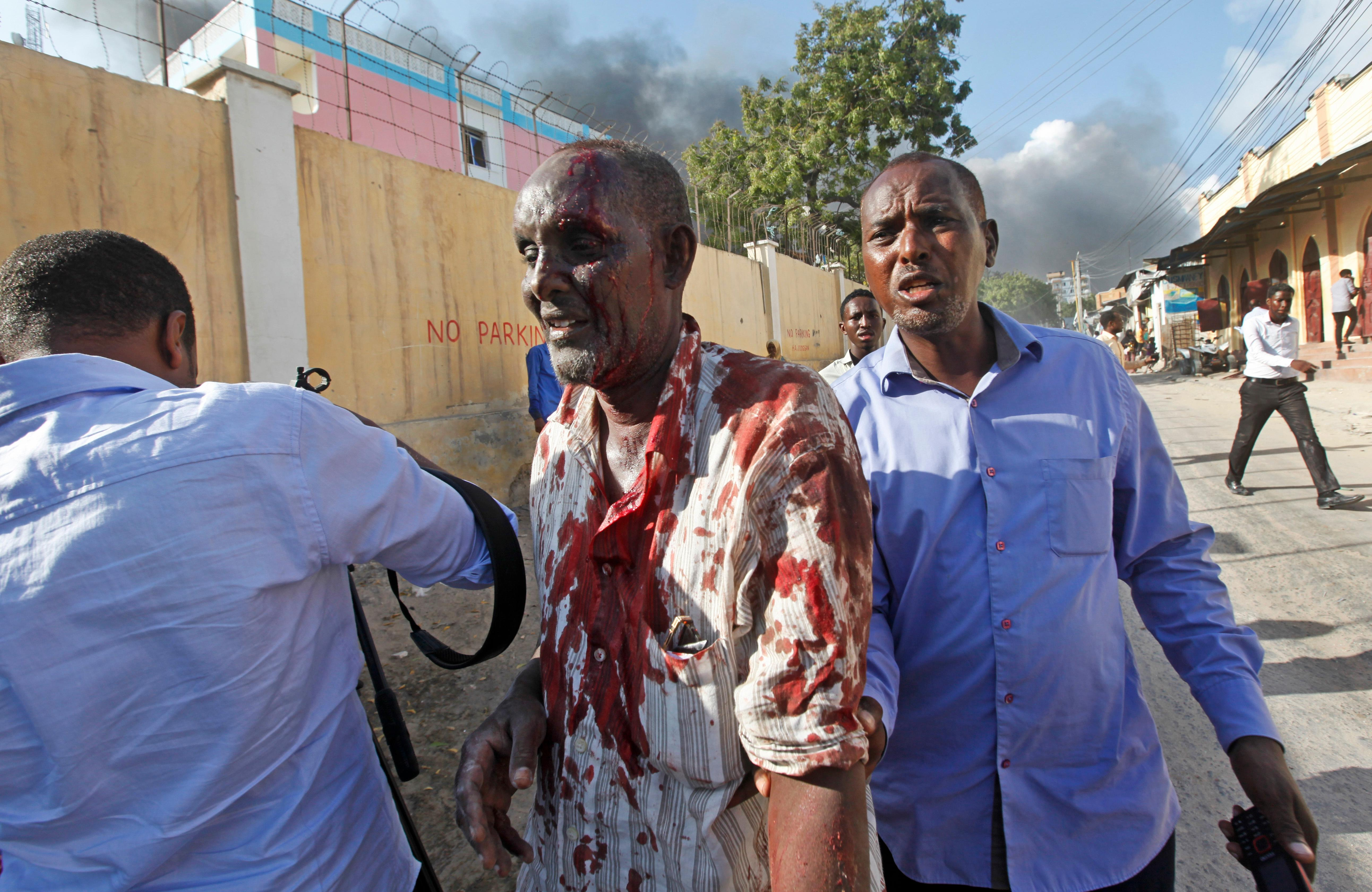 Somalis help a man wounded after a blast in the capital Mogadishu, Somalia Saturday, Oct. 14, 2017.  A huge explosion from a truck bomb has killed at least 20 people in Somalia's capital, police said Saturday, as shaken residents called it the most powerful blast they'd heard in years. (AP Photo/Farah Abdi Warsameh)