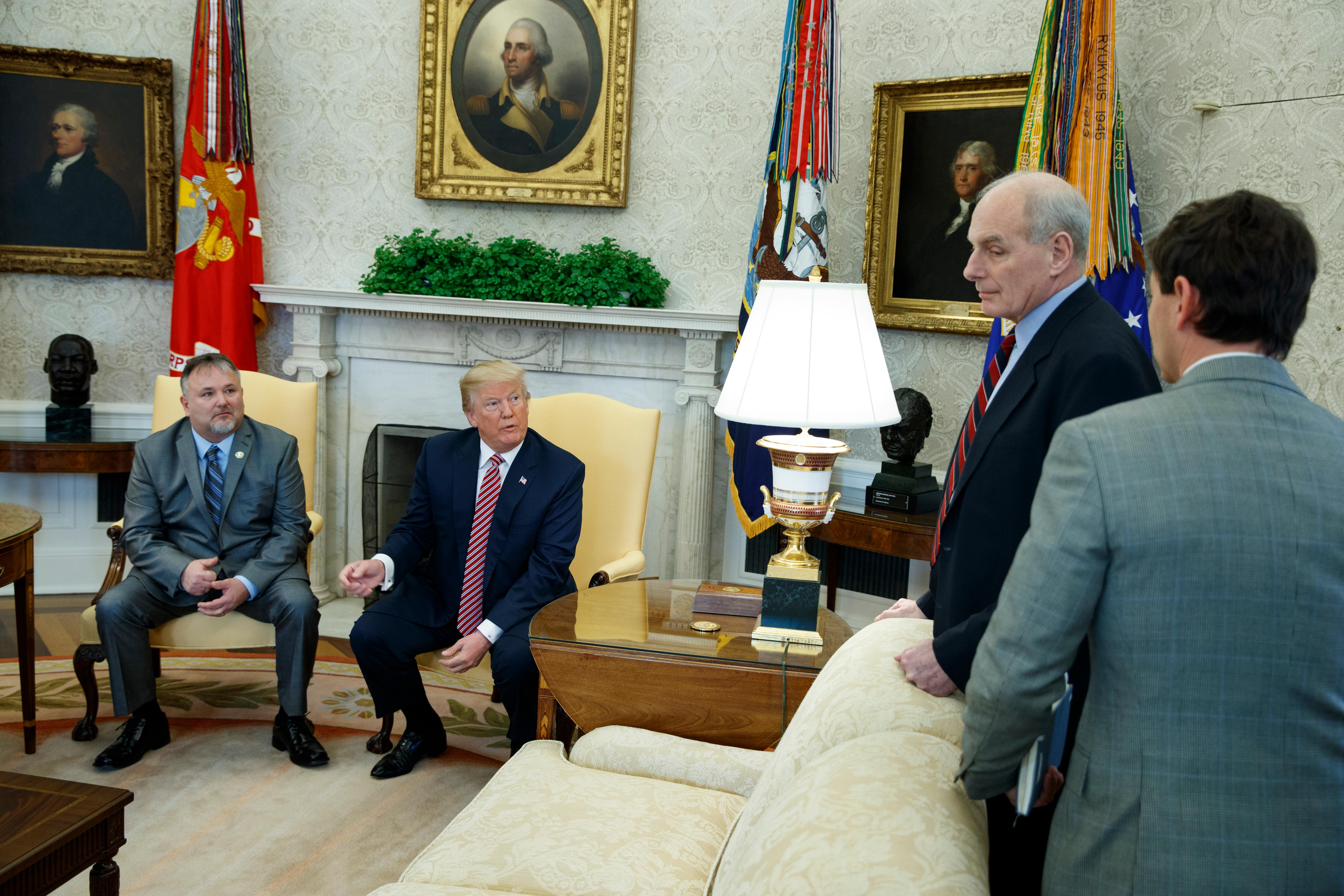 President Donald Trump speaks with White House Chief of Staff John Kelly, second from right, and White House deputy press secretary Hogan Gidley, right, after meeting with Don Bouvet, left, in the Oval Office of the White House, Friday, Feb. 9, 2018, in Washington. (AP Photo/Evan Vucci)