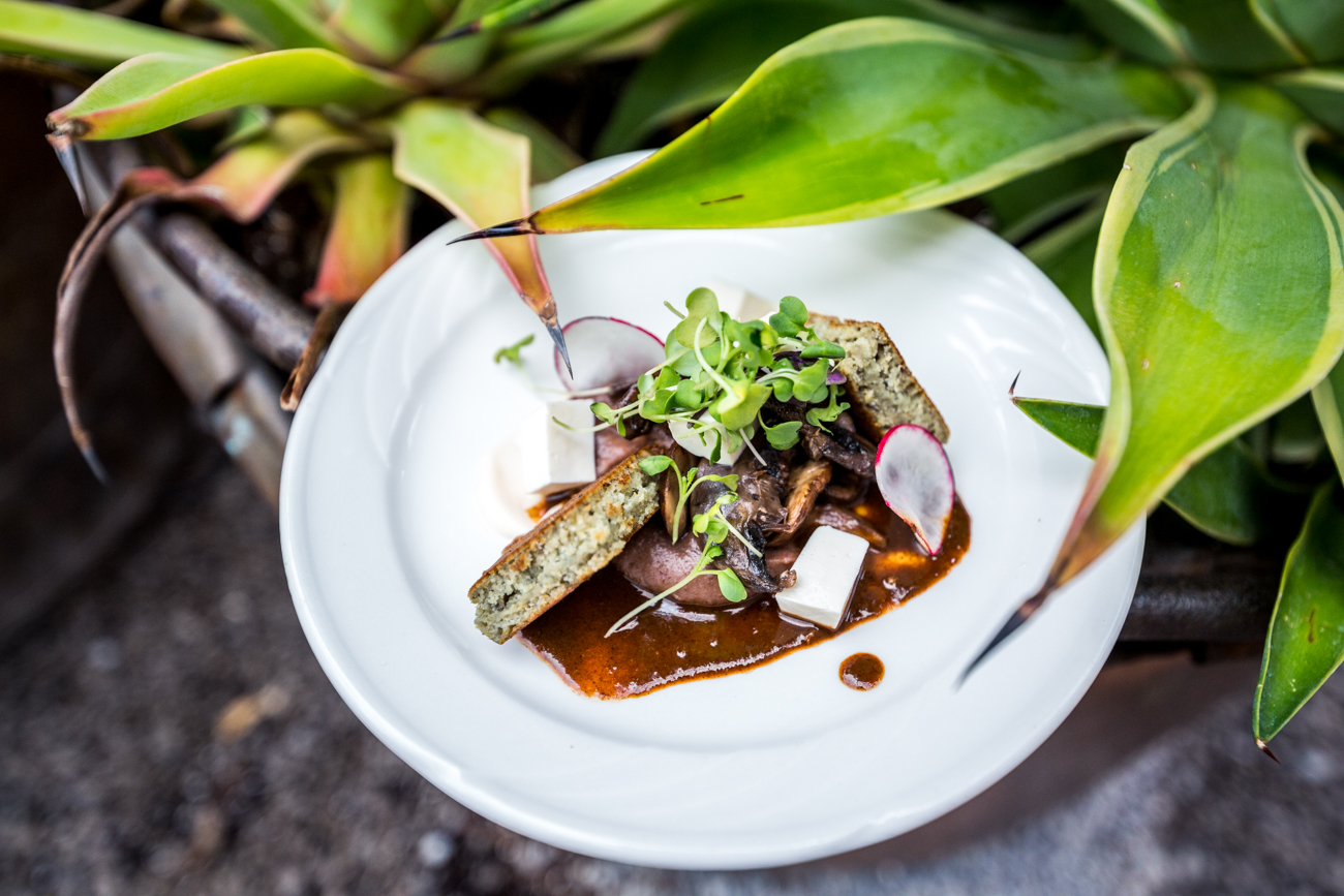 Vegetarian Mole Negro: panela, micro flowers, crema, salsa, bean puree, corn cake, queso fresco, radishes, and cilantro flowers / Image: Catherine Viox // Published: 6.18.19