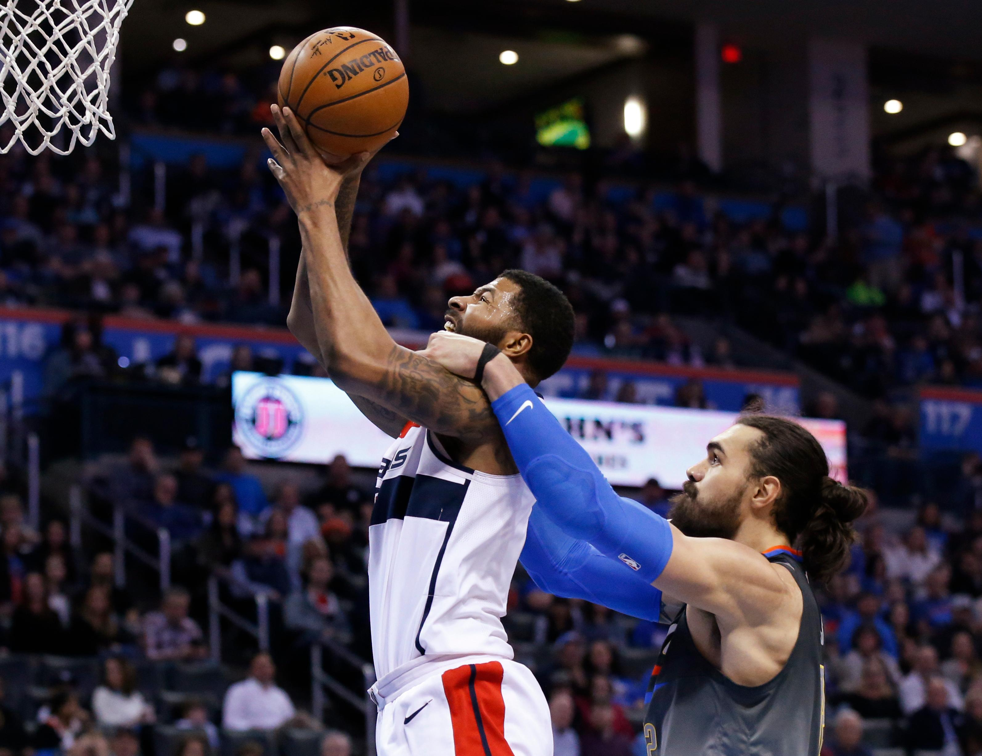 Washington Wizards forward Markieff Morris, left, is fouled by Oklahoma City Thunder center Steven Adams during the second quarter of an NBA basketball game in Oklahoma City, Thursday, Jan. 25, 2018. (AP Photo/Sue Ogrocki)