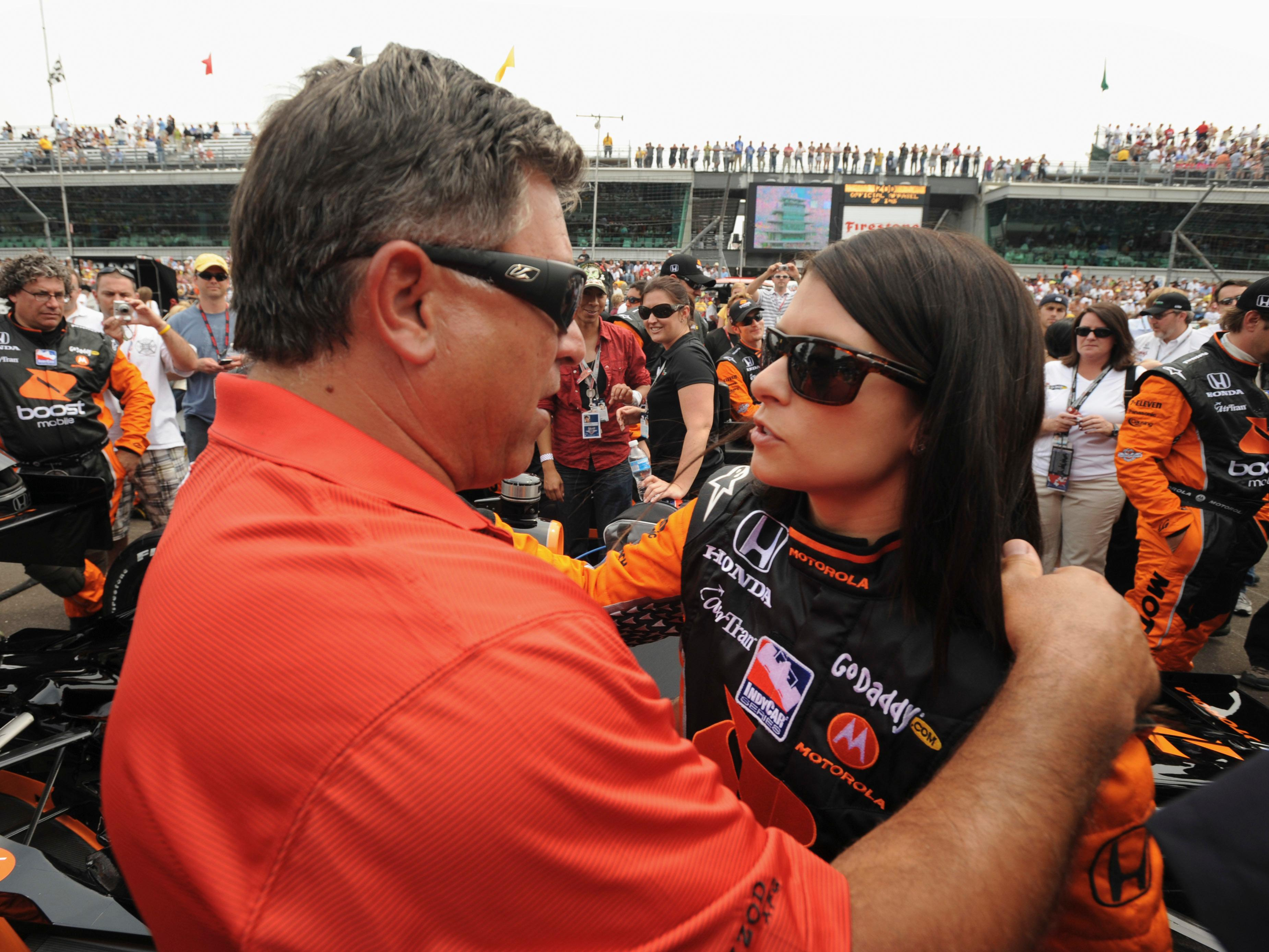 FILE - In this May 24, 2009, file photo, Danica Patrick, right, talks with her father T.J. Patrick before the 93rd running of the Indianapolis 500 auto race at the Indianapolis Motor Speedway in Indianapolis. Patrick announced plans Friday, Nov. 17, 2017, to run just 2 races in 2018, the Daytona 500 and the Indianapolis 500, and end her full-time driving career. (AP Photo/Tom Strickland, File)