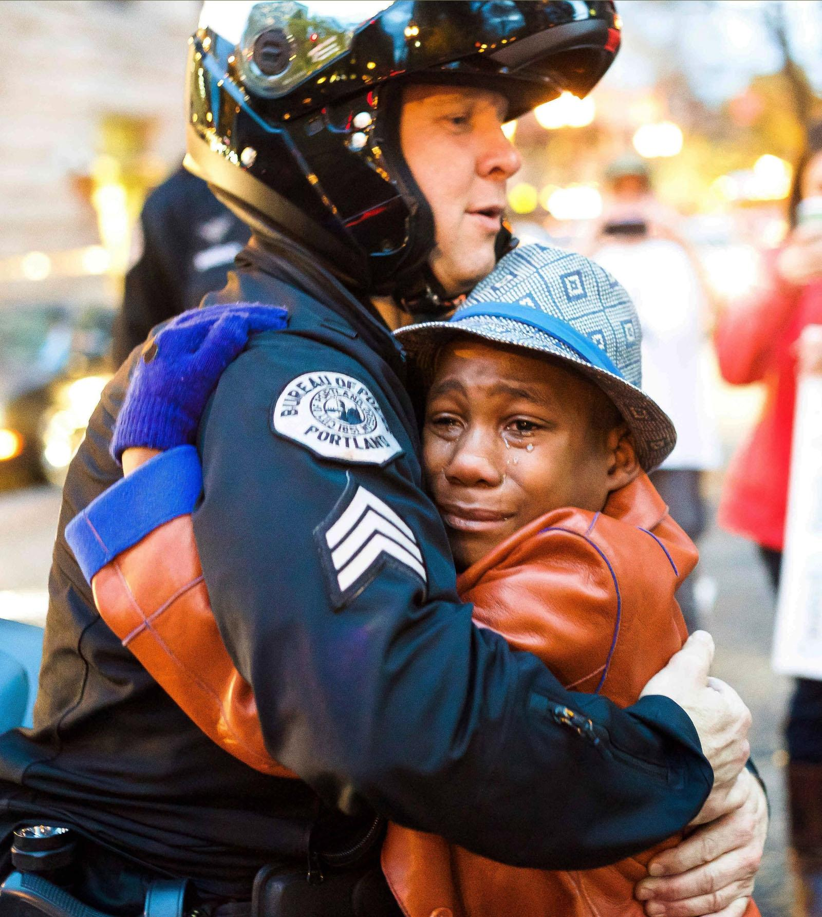 Portland police Sgt. Bret Barnum, left, and Devonte Hart, 12, hug at a rally Tuesday in Portland where people had gathered in support of the protests in Ferguson, Mo. AP Photo / Johnny Huu Nguyen