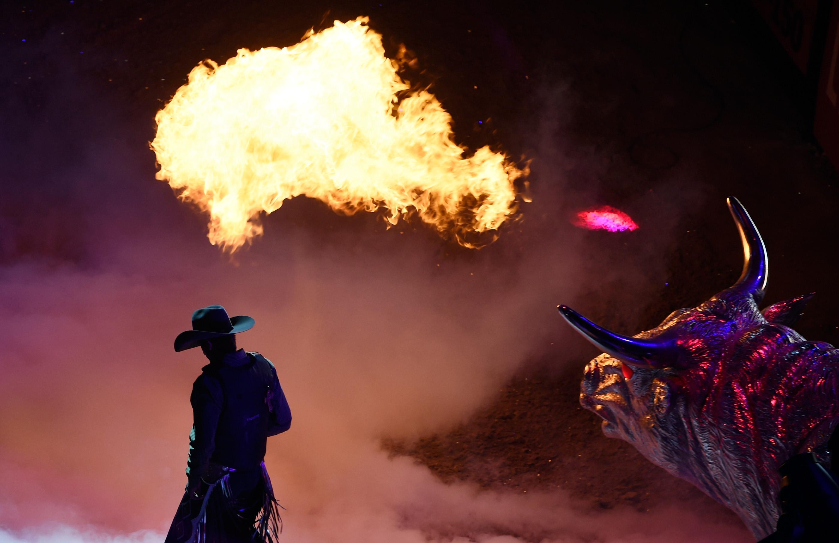 A bull rider introduced with a fire breathing bull statue before the start of the PBR World Finals at T-Mobile Arena Sunday, Nov. 5, 2017, in Las Vegas. [David Becker/Las Vegas News Bureau]