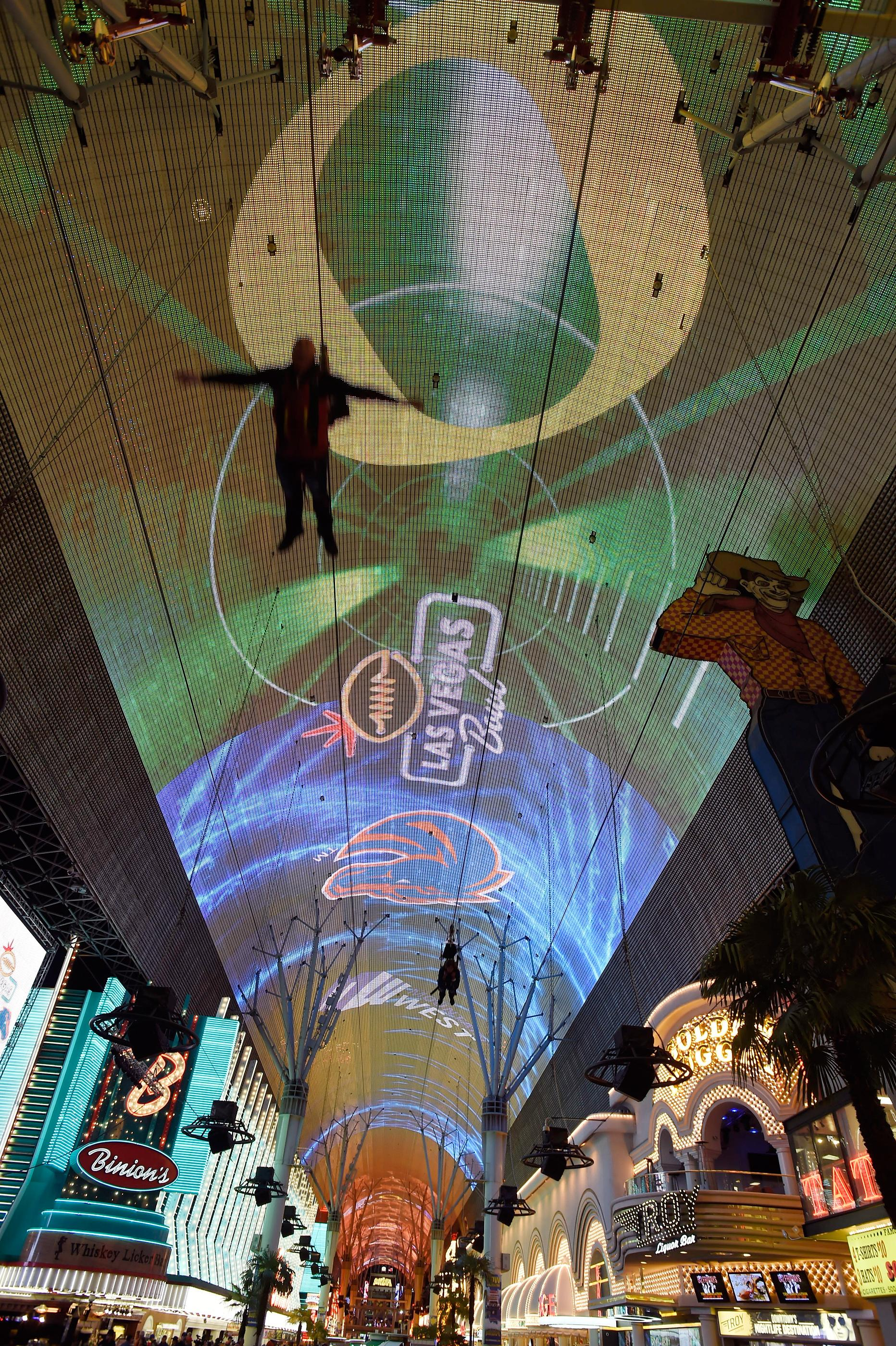 People glad along the zip line during before a pep rally at the Fremont Street Experience Friday, Dec. 15, 2017, in Las Vegas. The Boise State Bronco will take on the Oregon Ducks in the 26th edition of the Las Vegas Bowl at Sam Boyd Stadium on Saturday. CREDIT: David Becker/Las Vegas News Bureau