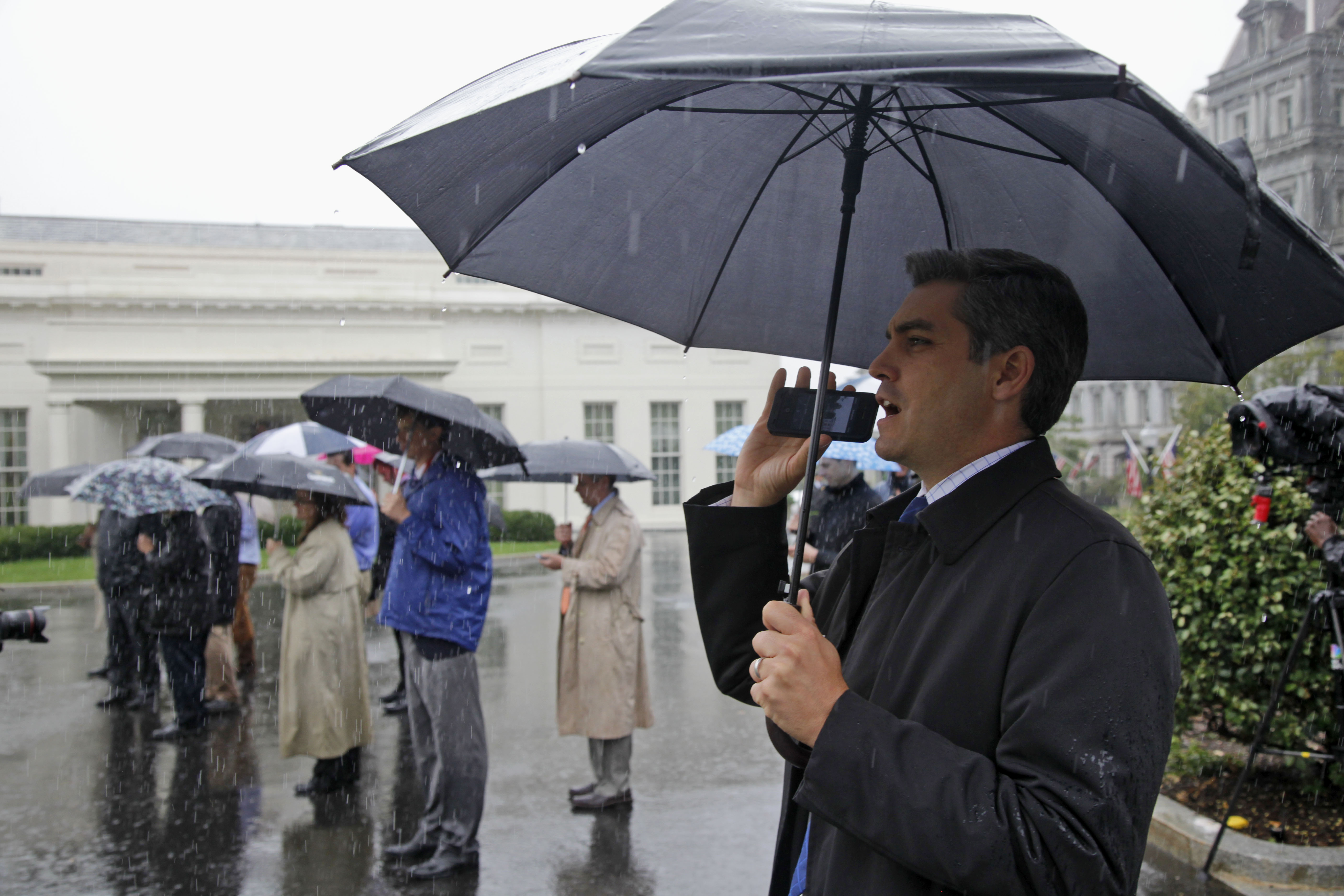 Jim Acosta of CNN shouts questions as he waits with other reporters in the rain outside the White House in Washington, Friday, Oct. 11, 2013, as Republican senators leave from the North Portico without speaking to reporters after meeting with President Barack Obama regarding the government shutdown and debt ceiling. (AP Photo/Charles Dharapak)