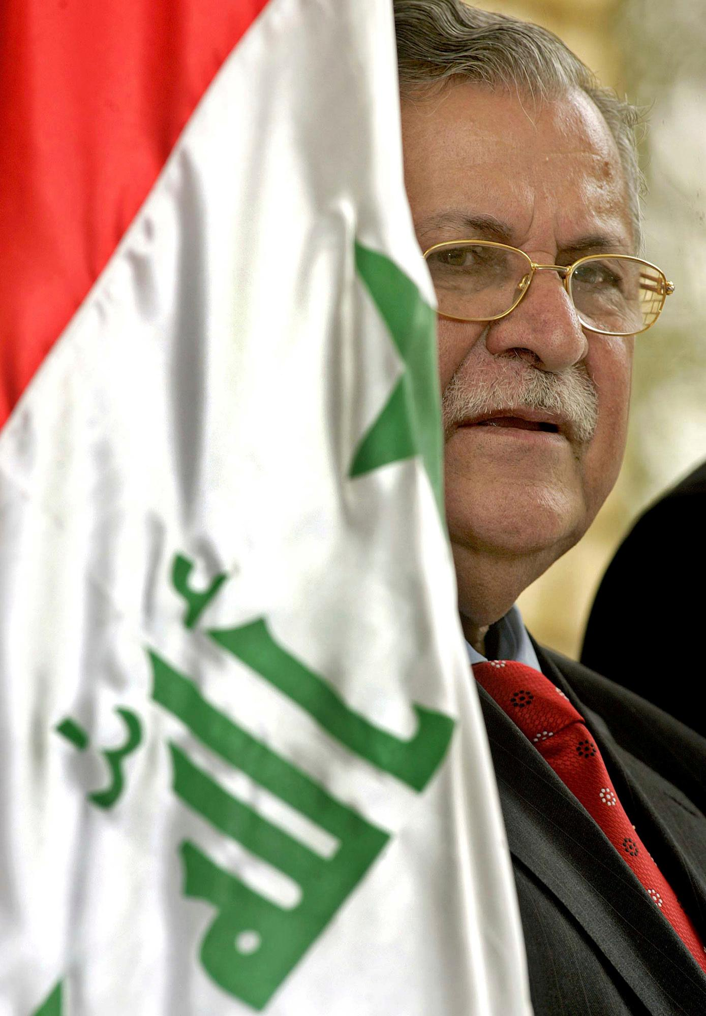 FILE - In this July 23, 2005, file photo, Iraqi President Jalal Talabani peers from behind the Iraqi flag during a press briefing with US Ambassador to Iraq Zalmay Khalilzadat Talabani's residence in Baghdad, Iraq. Talabani, a lifelong fighter for Iraq's Kurds who rose to become the country's president, presenting himself as a unifying father figure to temper the potentially explosive hatreds among Kurds, Shiites and Sunnis has died in a Berlin hospital at the age of 83. (AP Photo/Liu Jin, Pool, File)