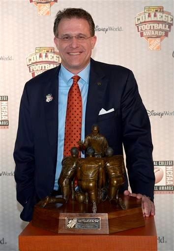 Auburn head coach Gus Malzahn poses with The Home Depot Coach of the Year Award after winning the honor during the College Football Awards show in Lake Buena Vista, Fla., Thursday, Dec. 12, 2013.