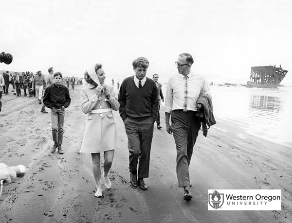 Senator Robert F. Kennedy, wife Ethel Kennedy, and Oregon State Treasurer Robert W. Straub walk together on the beach near Fort Stevens State Park. In the background are the remains of the Peter Iredale shipwreck and a crowd of people. The photo was taken on Kennedy's visit before the 1968 Oregon primary election shortly before his assassination. (Western Oregon University Archives - Robert W. Straub Collection/Used with permission)
