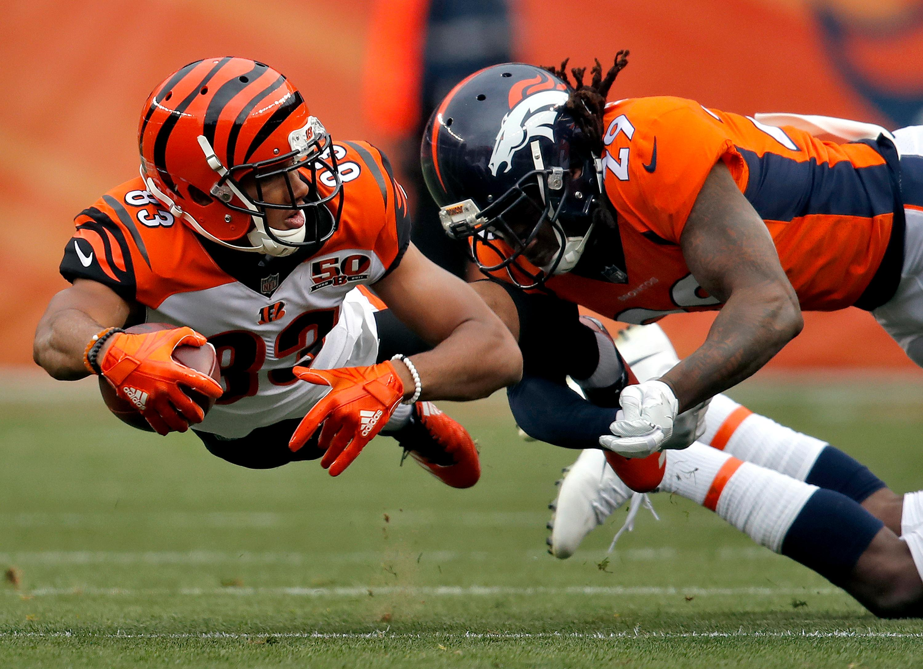 Cincinnati Bengals wide receiver Tyler Boyd (83) lunges for yards as Denver Broncos free safety Bradley Roby (29) makes the hit during the first half of an NFL football game, Sunday, Nov. 19, 2017, in Denver. (AP Photo/David Zalubowski)