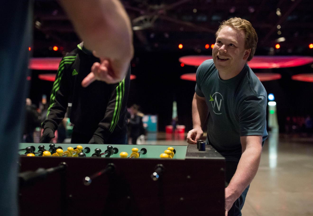 Navigating Cancer employee Skylar Broad retrieves the foosball during a game against coworkers at the 6th annual Geekwire Bash at the CenturyLink Event Center. (Sy Bean / Seattle Refined)