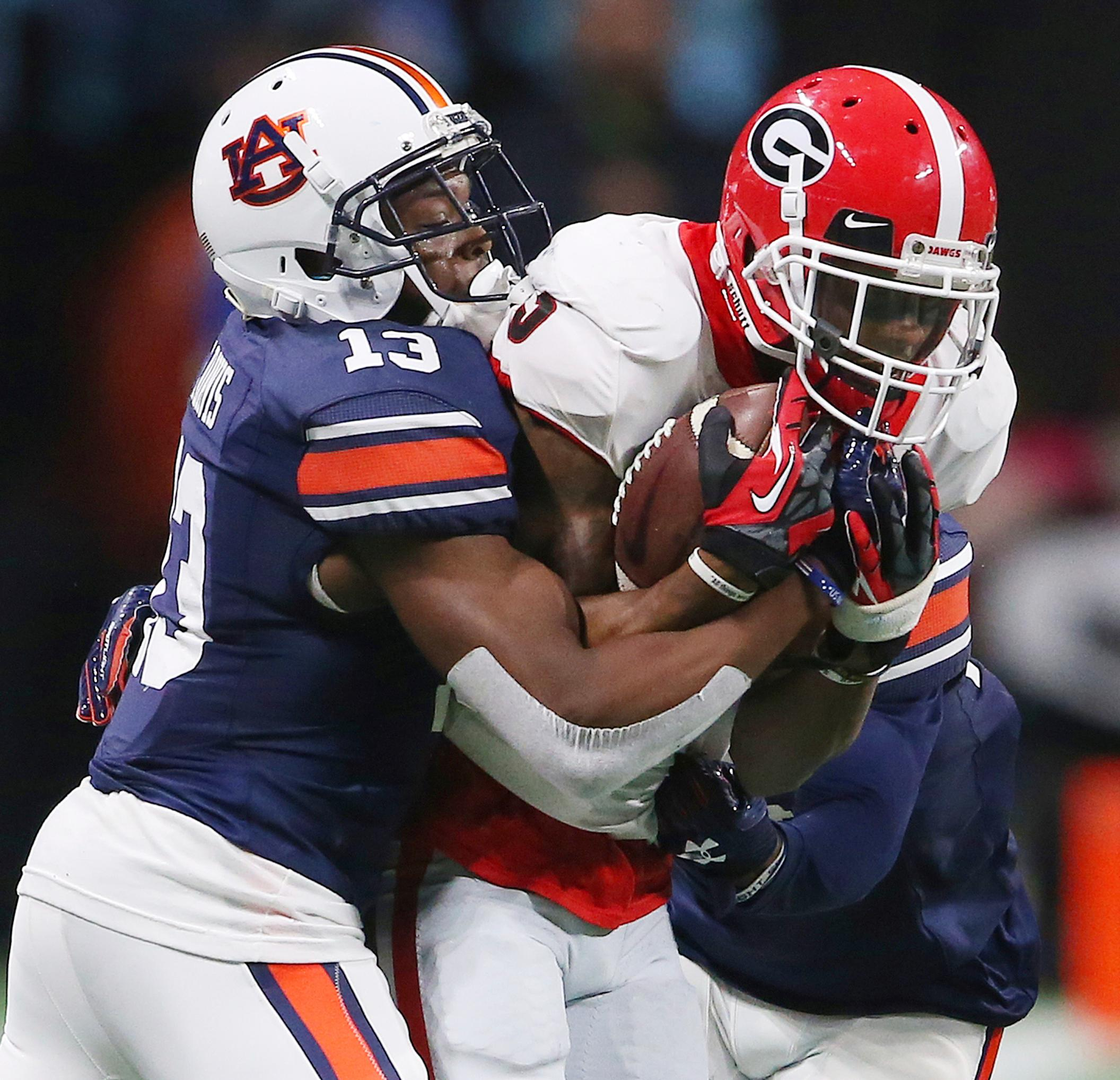 Auburn defensive back Javaris Davis (13) tackles Georgia wide receiver Terry Godwin (5) during the second half of the Southeastern Conference championship NCAA college football game, Saturday, Dec. 2, 2017, in Atlanta. (AP Photo/John Bazemore)