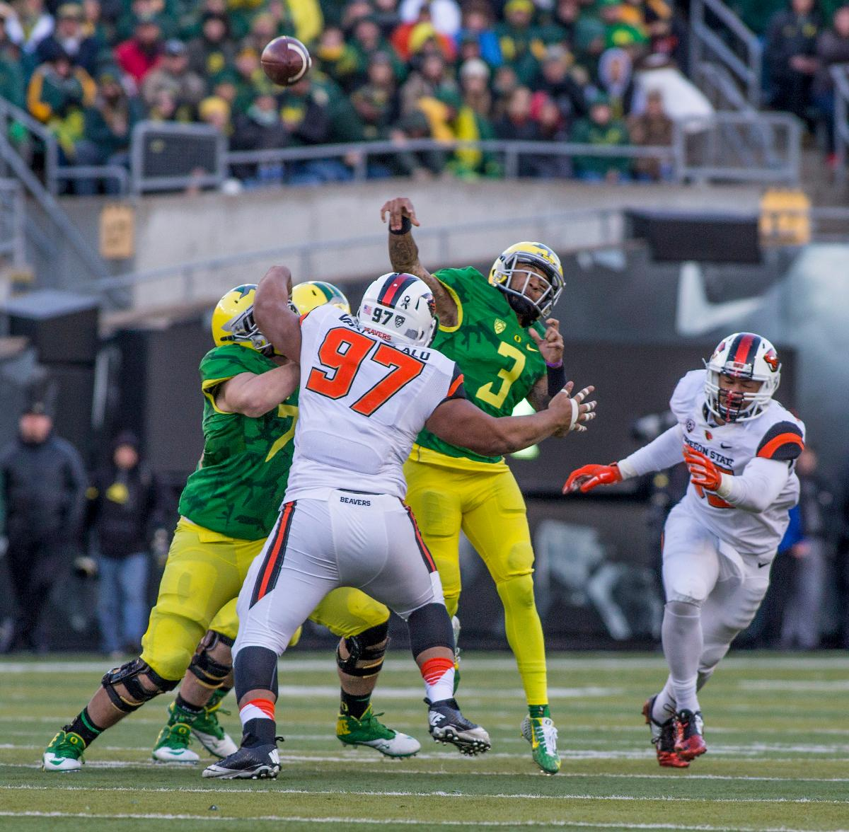 Oregon Ducks quarterback Vernon Adams Jr. (#3) throws the ball just before he�s tackled by Oregon State Beavers Kalani Vakameilalo (#97). The Oregon Ducks beat the Oregon State Beavers 52-42 in the 119th Civil War for the eighth year in a row at Autzen Stadium on Friday afternoon. Katie Pietzold, Oregon News Lab