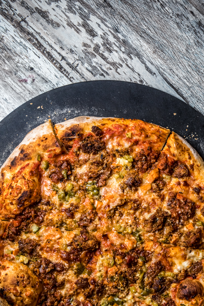 Rick's Spicy Sausage Pizza topped with bolognese sauce, parmesan and fontinella cheese, house-made sausage, and pepper relish / Image: Catherine Viox{ }// Published: 4.21.20