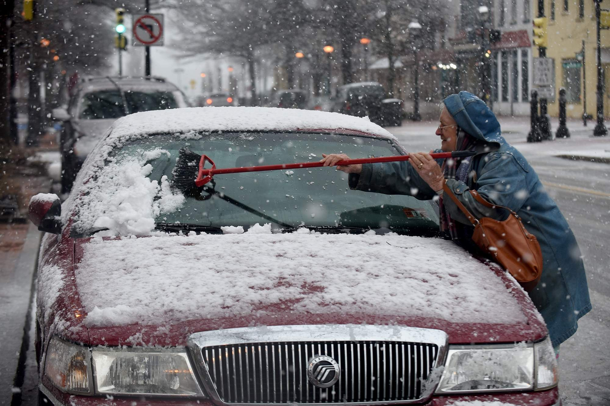 Pat Measey of Burlington City cleans snow off her car on High Street in Burlington City on Wednesday, March 7, 2018. [CARL KOSOLA / STAFF PHOTOJOURNALIST]
