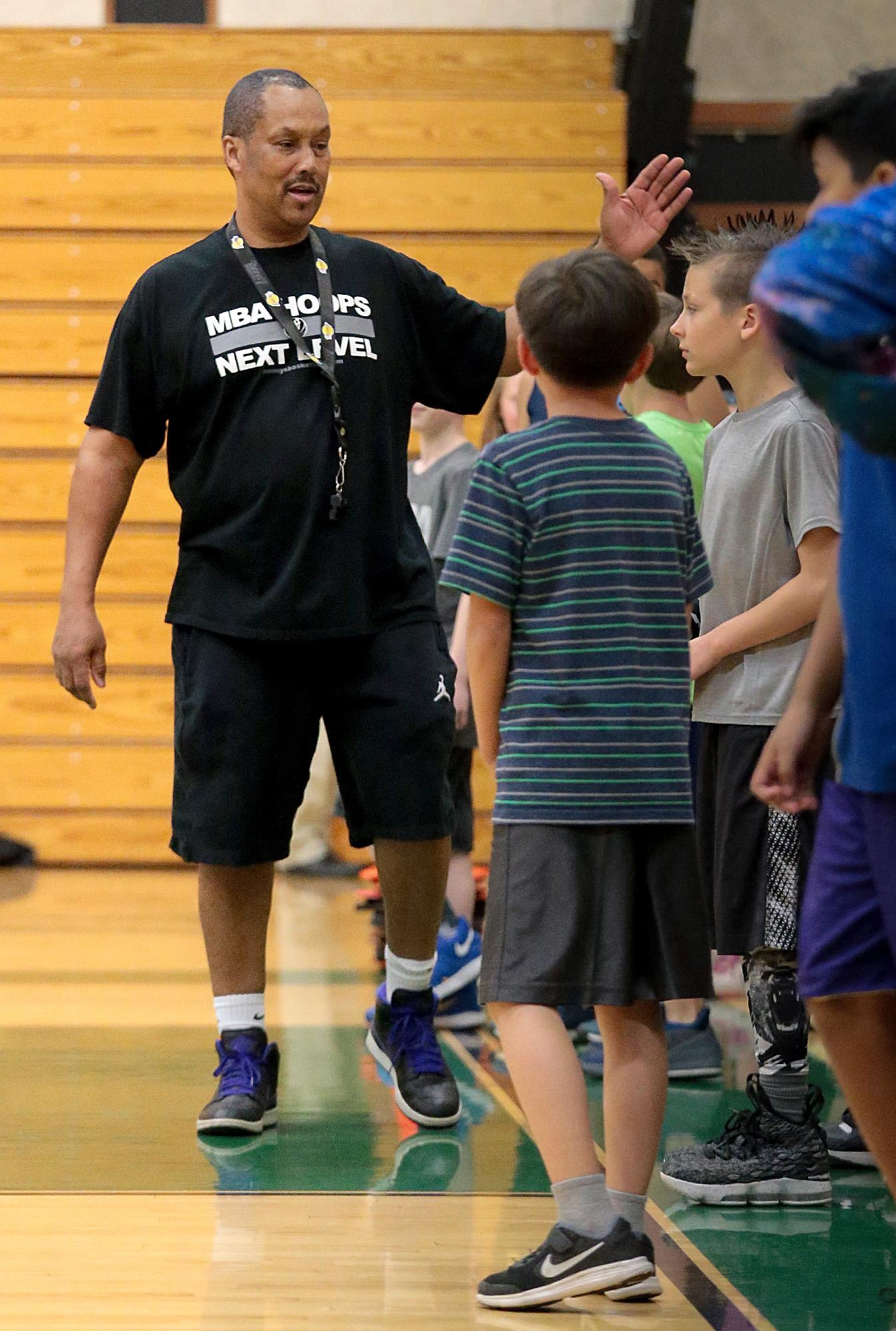 Manny Crump, working with kids during an MBA Hoops session at Central High gym on Wednesday.[PHOTO BY:  LARRY STAUTH JR]