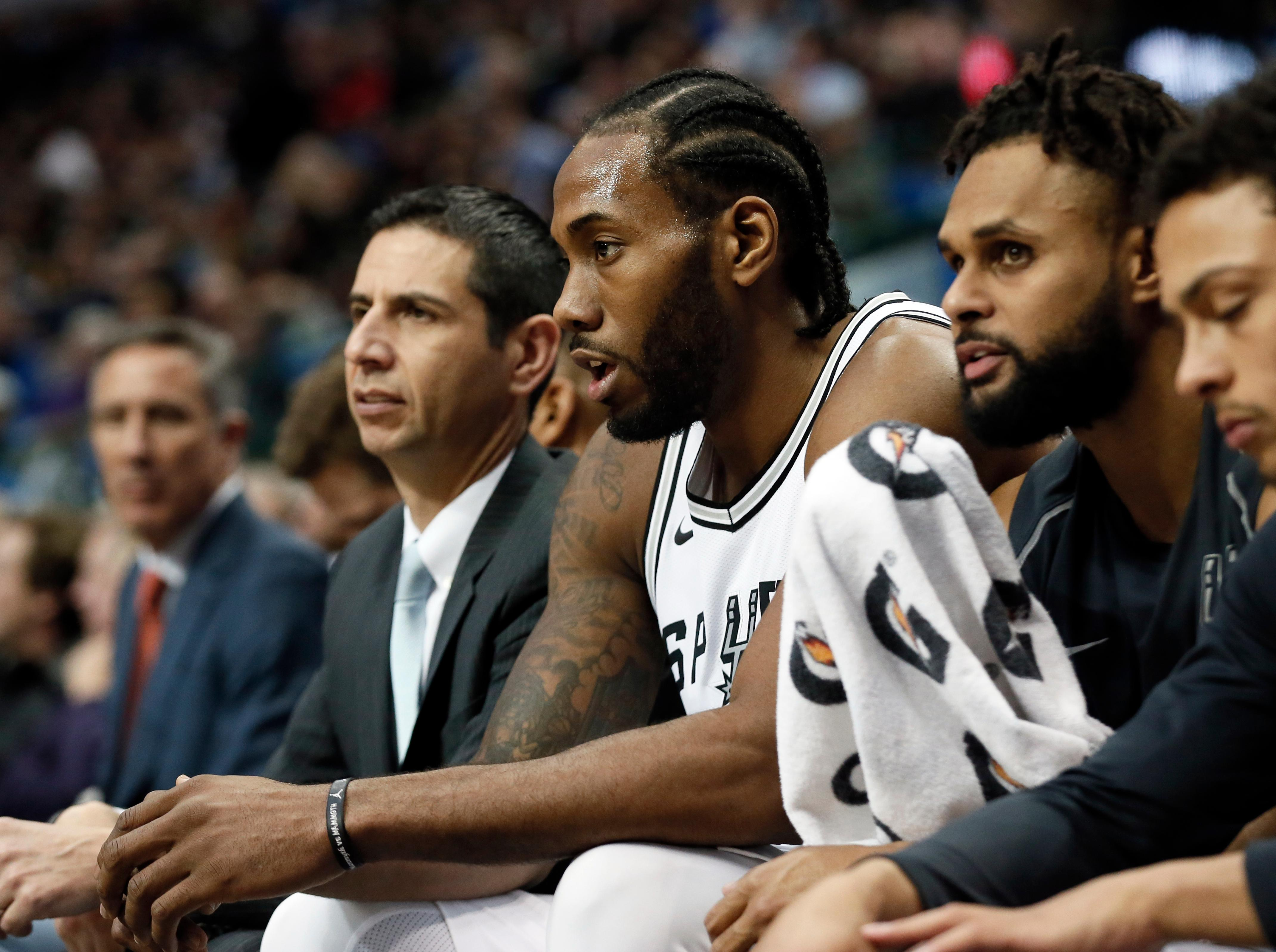 San Antonio Spurs' Kawhi Leonard, center, sits on the bench after playing in the first half of an NBA basketball game against the Dallas Mavericks on Tuesday, Dec. 12, 2017, in Dallas. (AP Photo/Tony Gutierrez)
