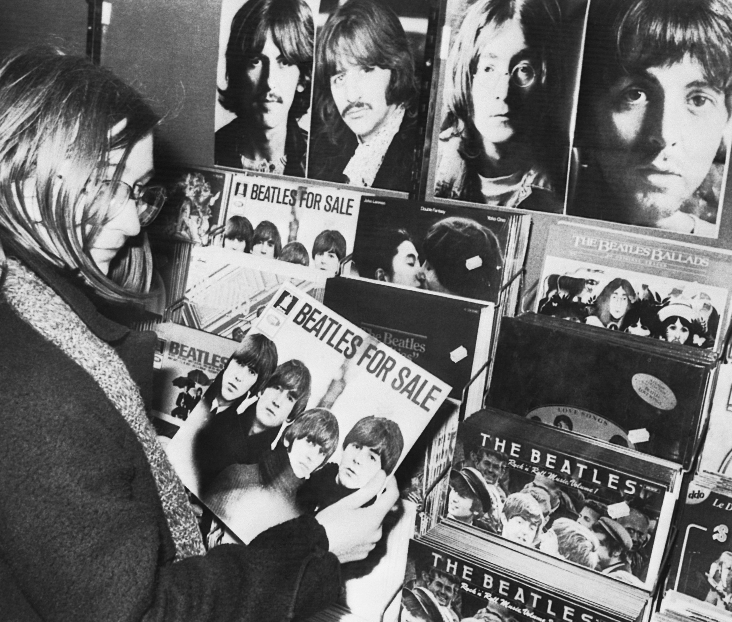 In this Dec. 10, 1980 file photo, a fan of British pop group The Beatles holds a vintage record album Beatles for Sale in a record shop in Stuttgart, Germany.A special stand with portraits of the four members of the group and all available records was erected this morning in memory of John Lennon who was killed in New York City. Thirty-five years ago on Dec. 8, Mark David Chapman shot and killed Lennon, a former Beatles member. (AP Photo/Thomas Meyer, File)