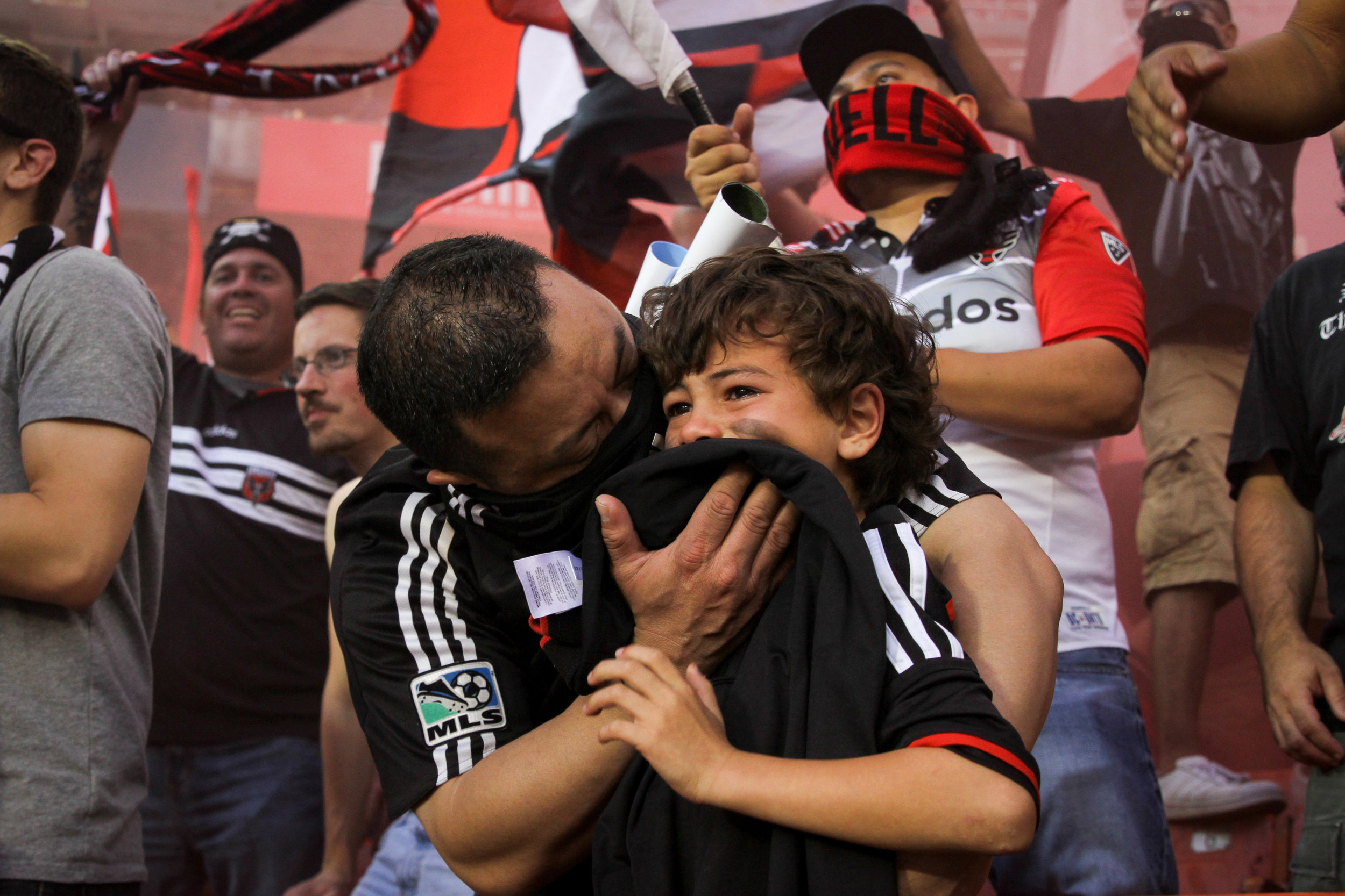 A man shields his son's face as smoke bombs cloud the air at DC United's last game at Robert F. Kennedy Stadium in Washington, D.C.. (Amanda Andrade-Rhoades/DC Refined)